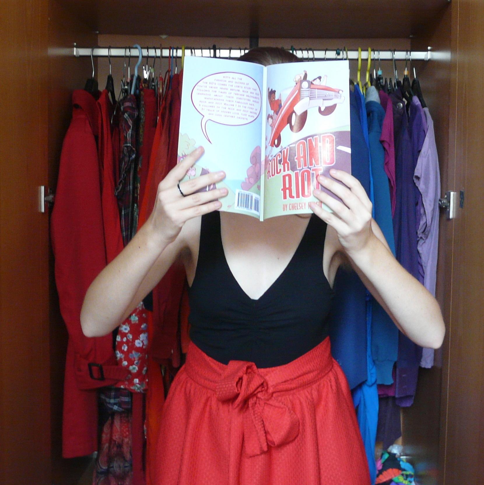 personne en tenue de danse rock rouge et noire lisant Rock and Riot devant un placard ouvert sur des vêtements arc-en-ciel