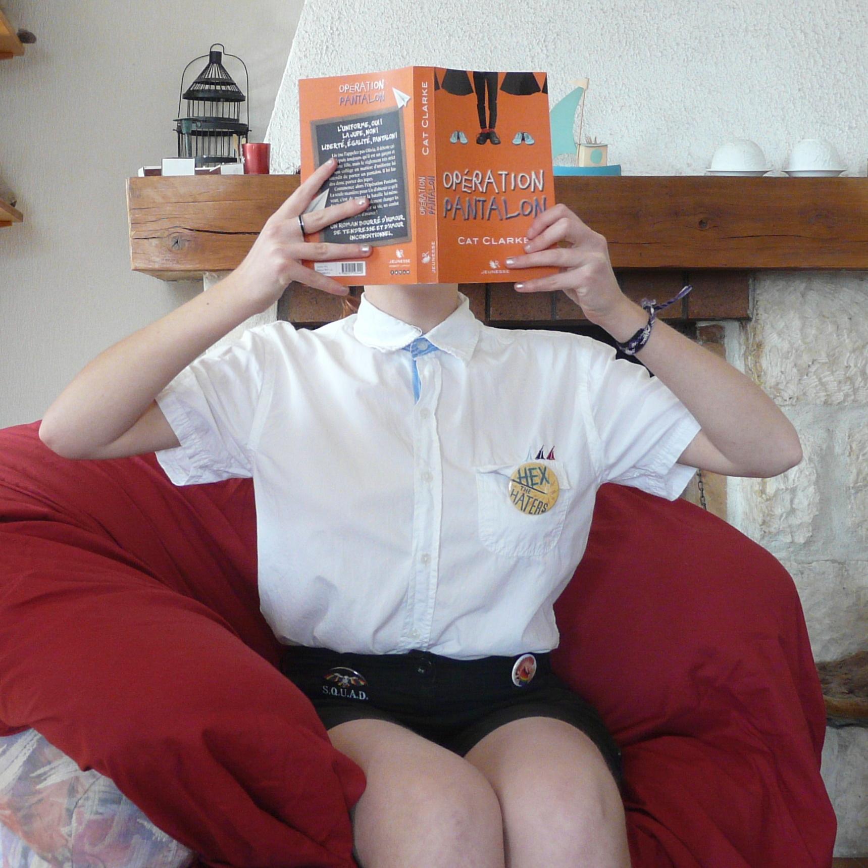 personne en chemise et short lisant Opération Pantalon dans un fauteuil devant la cheminée