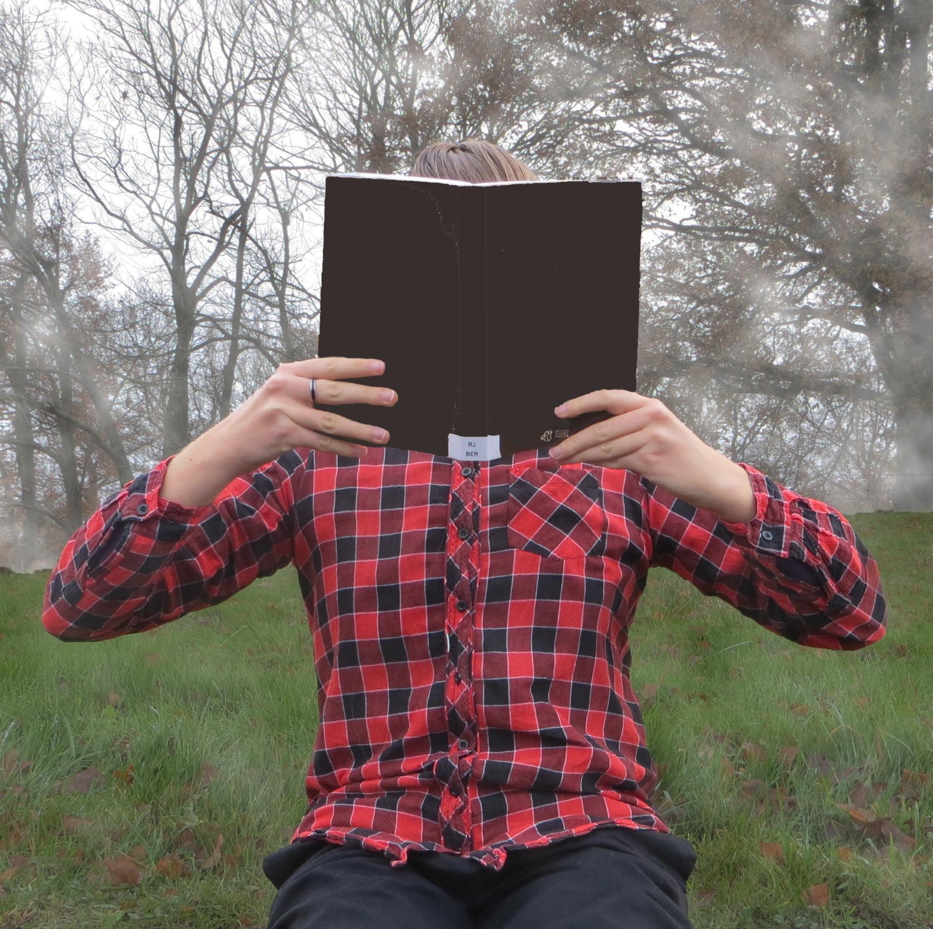 personne en chemise à carreaux lisant un livre noir dans la brume