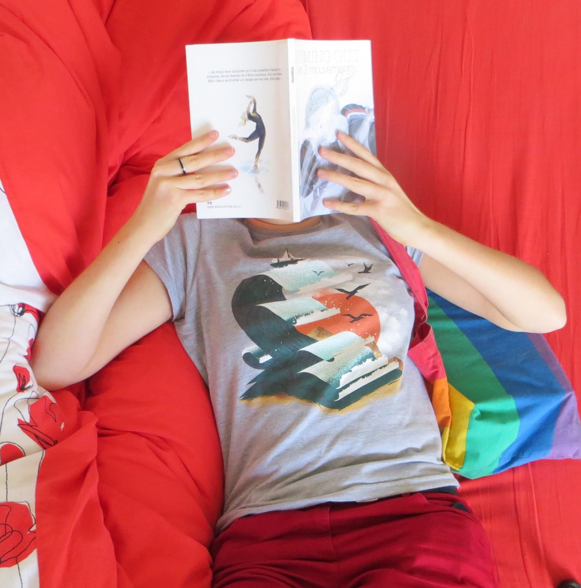 personne lisant coming-out en deux mouvements allongée sur un lit rouge