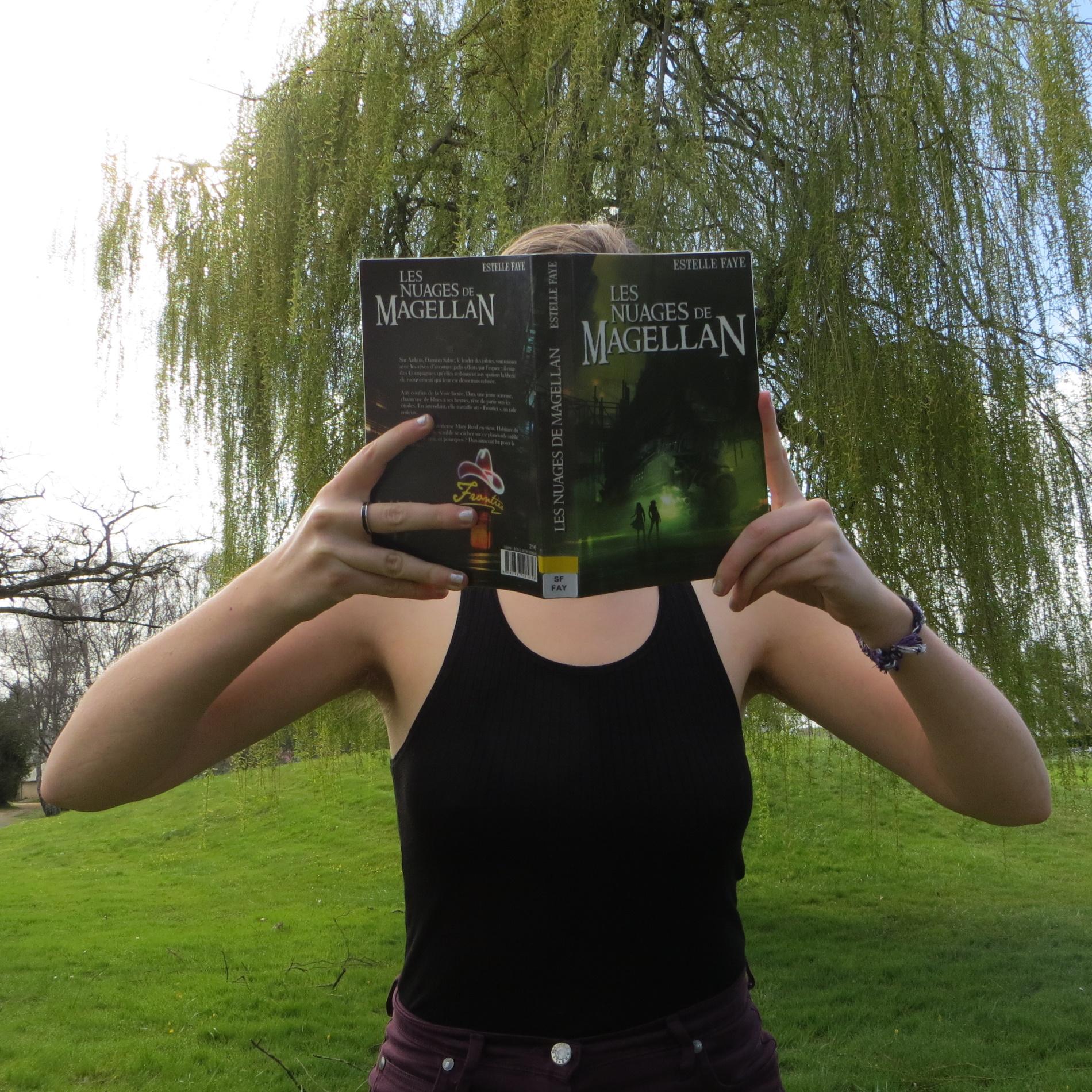 personne en débardeur lisant Les Nuages de Magellan devant un saule pleureur
