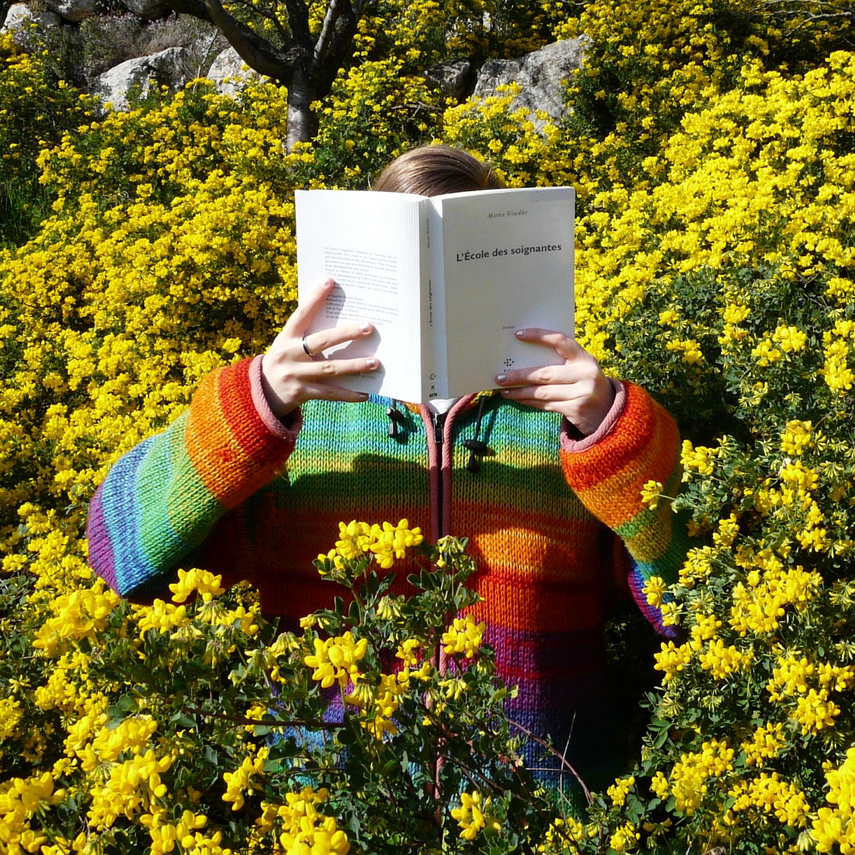 personne en manteau arc-en-ciel lisant l'école des Soignantes de Martin Winckler au milieu de buissons de fleurs jaunes