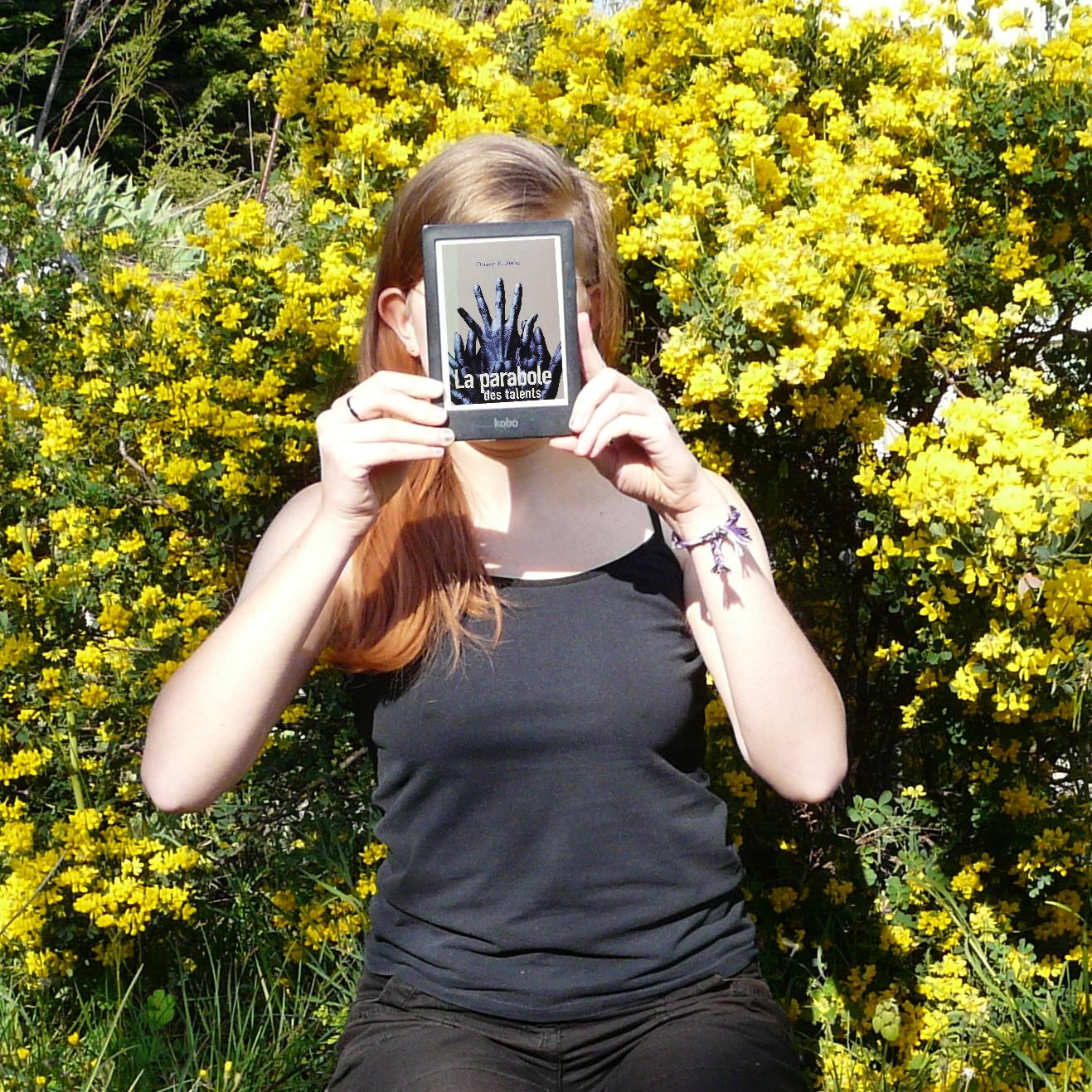 personne en noir lisant la Parabole des Talents devant un massif de fleurs jaunes