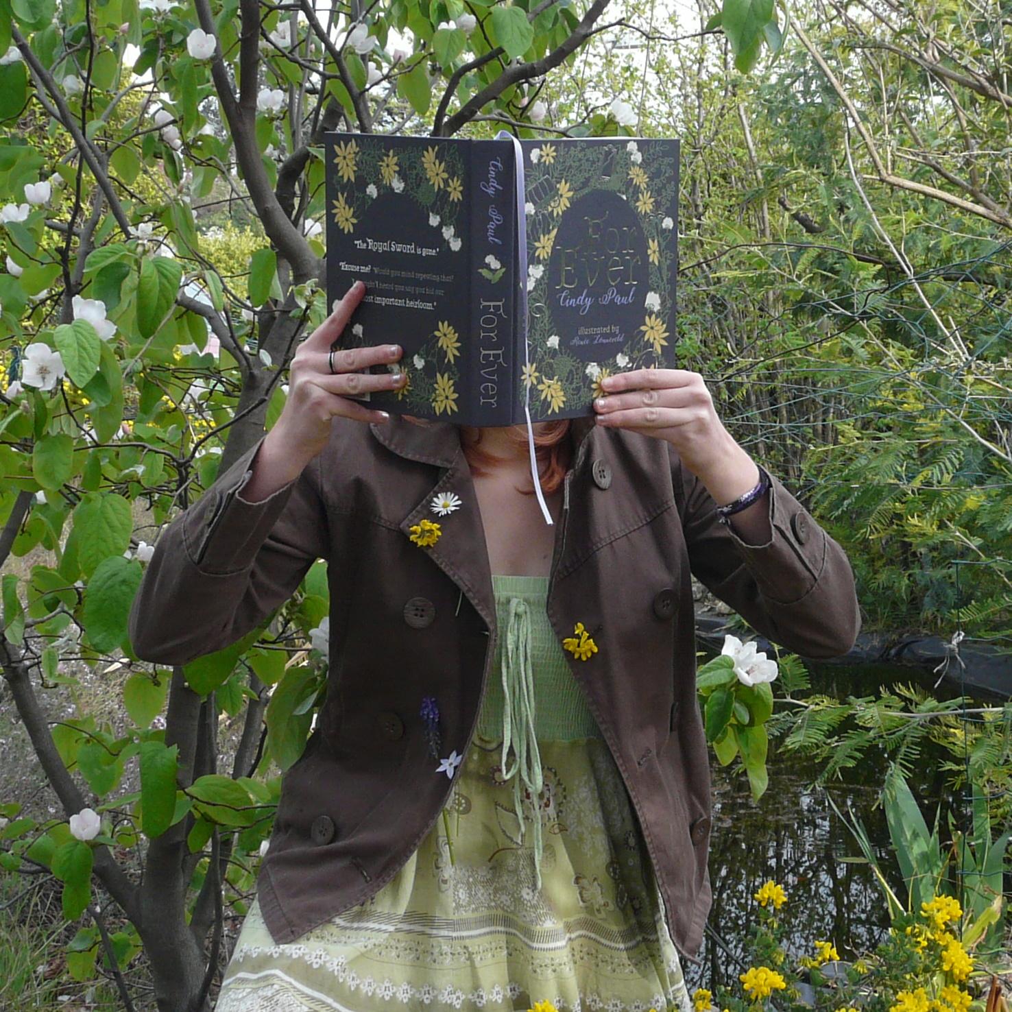 personne en robe verte et veste brune décorée de fleurs lisant For Ever devant un étang