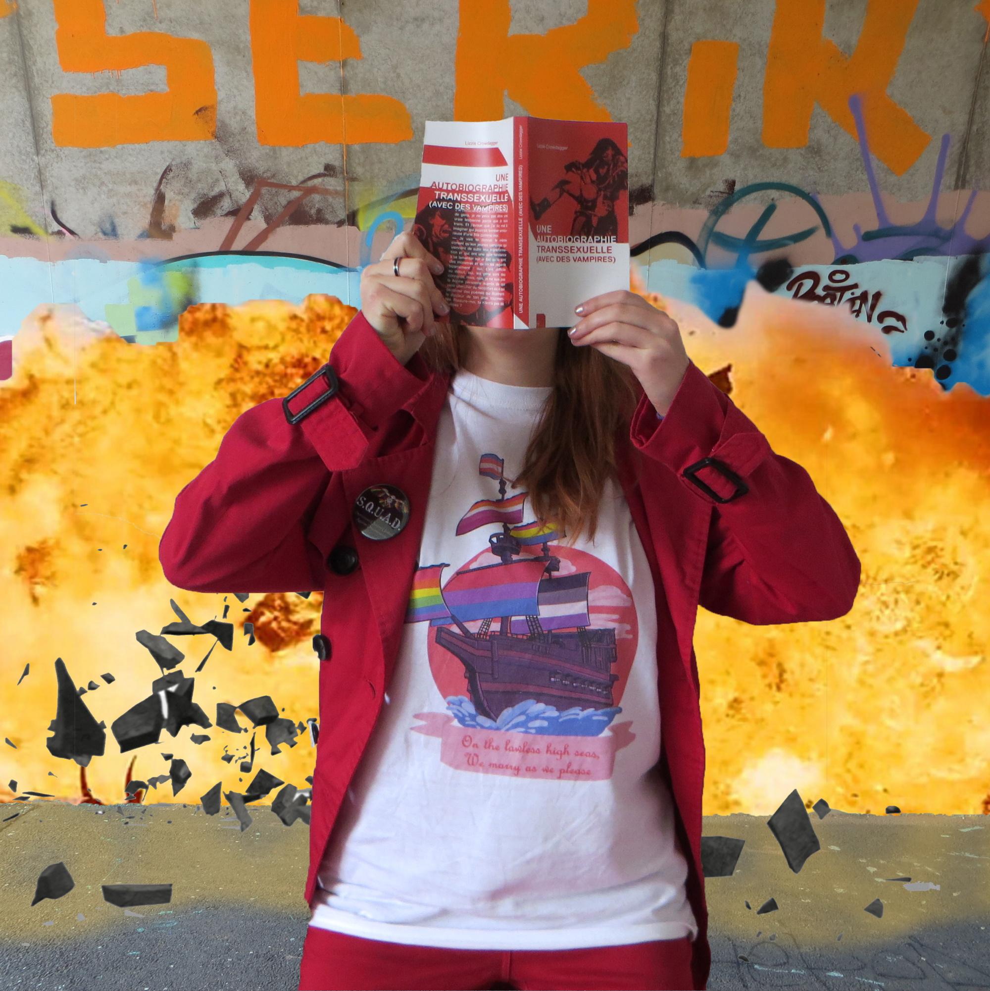 personne en t-shirt pirate queer et parka rouge lisant Une autobiographie transssexuelle (avec des vampires) de Lizzie Crowdagger devant un mur tagué qui explose