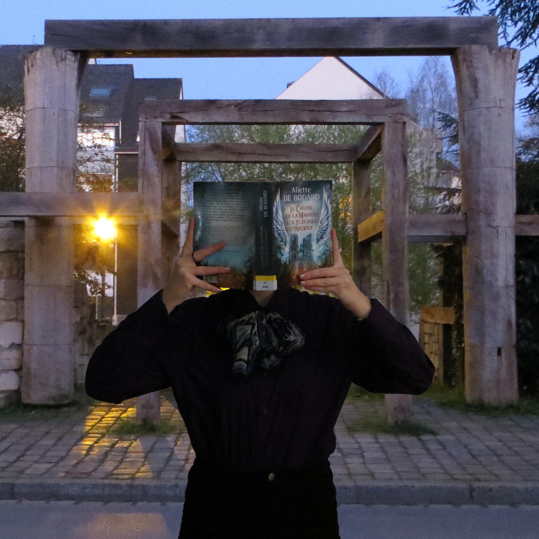 personne en tenue chic lisant La Chute de la Maison aux Flèches d'Argent devant une structure de bois