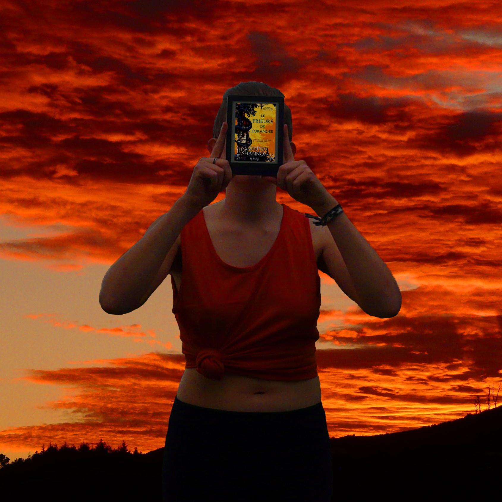 personne en débardeur lisant Le Prieuré de l'Oranger devant un coucher de soleil intense