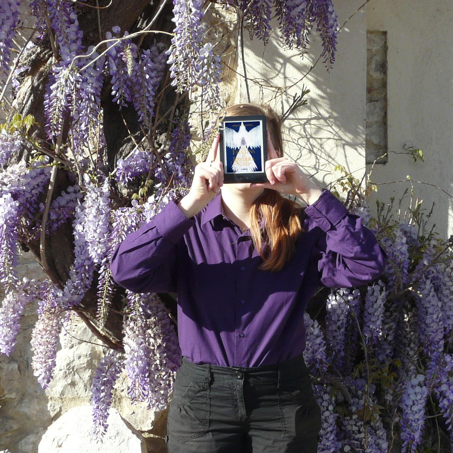 personne en chemise violette lisant L'héritière Rebelle de Melissa Caruso devant une vigne tortueuse couverte de fleurs violettes