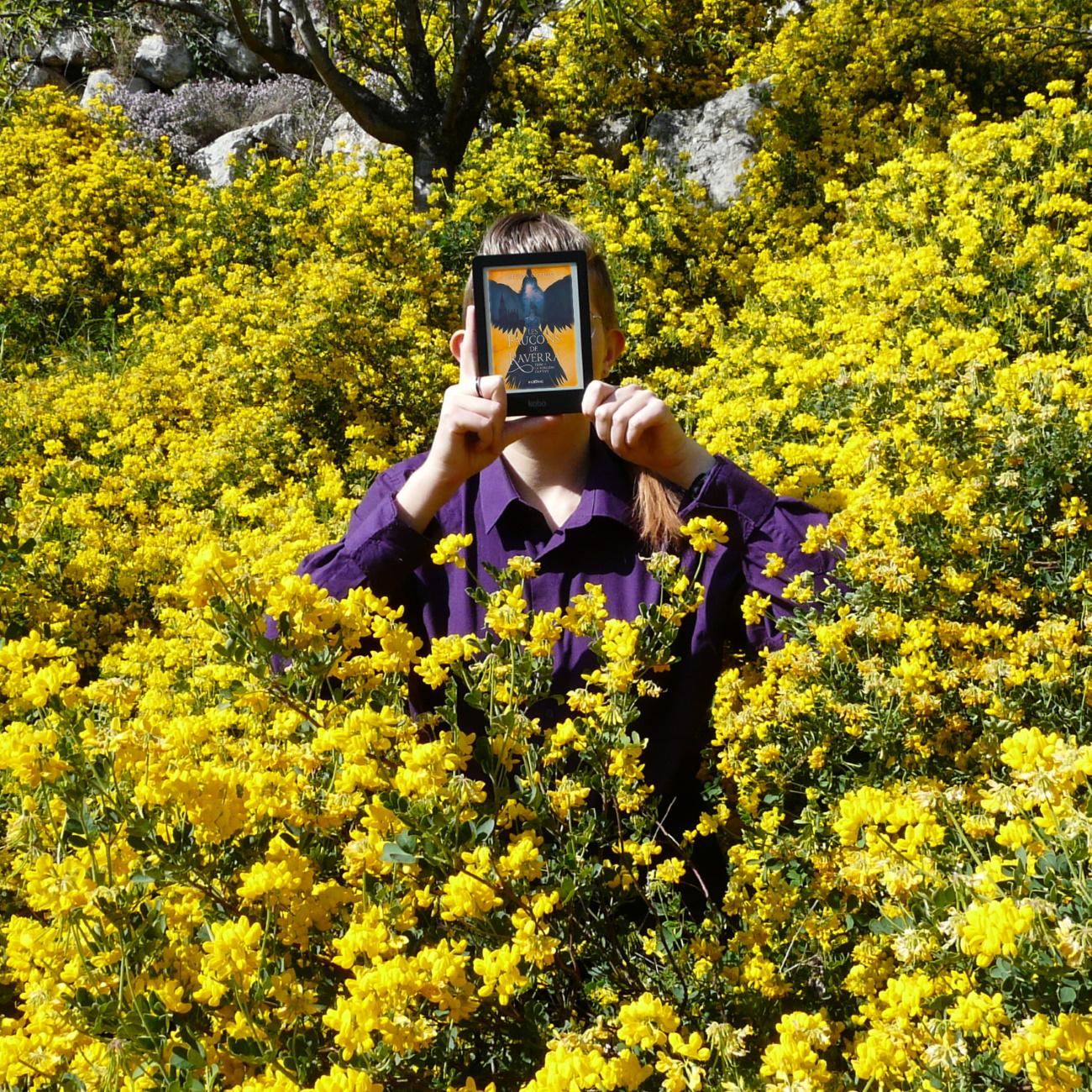 personne en chemise violette lisant Les Faucons de Raverra au milieu de fleurs jaunes