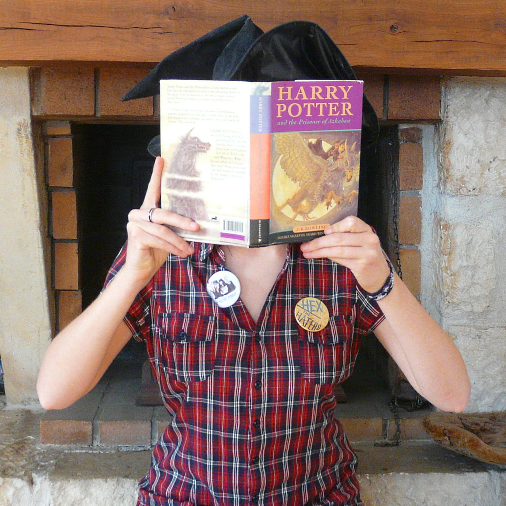 sorcière lisant Harry potter devant une cheminée