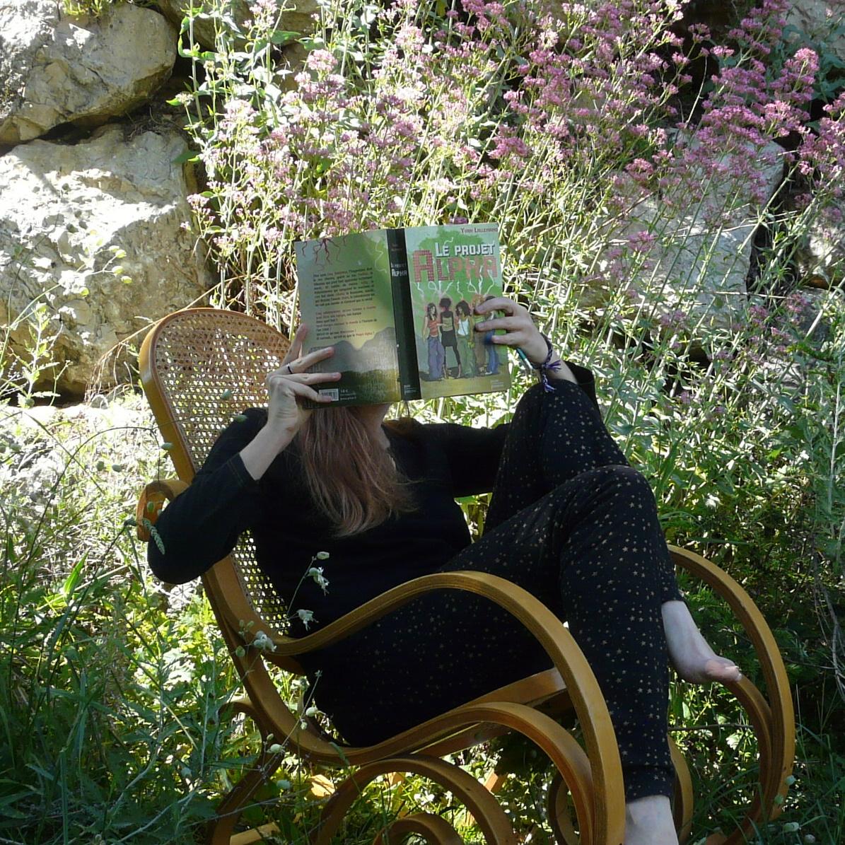 personne en pyjama étoilé lisant Le Projet Alpha dans une chaise à bascule