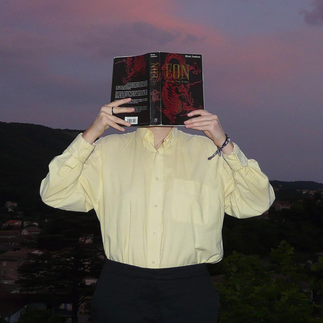 personne en chemise jaune lisant Eon devant un coucher de soleil