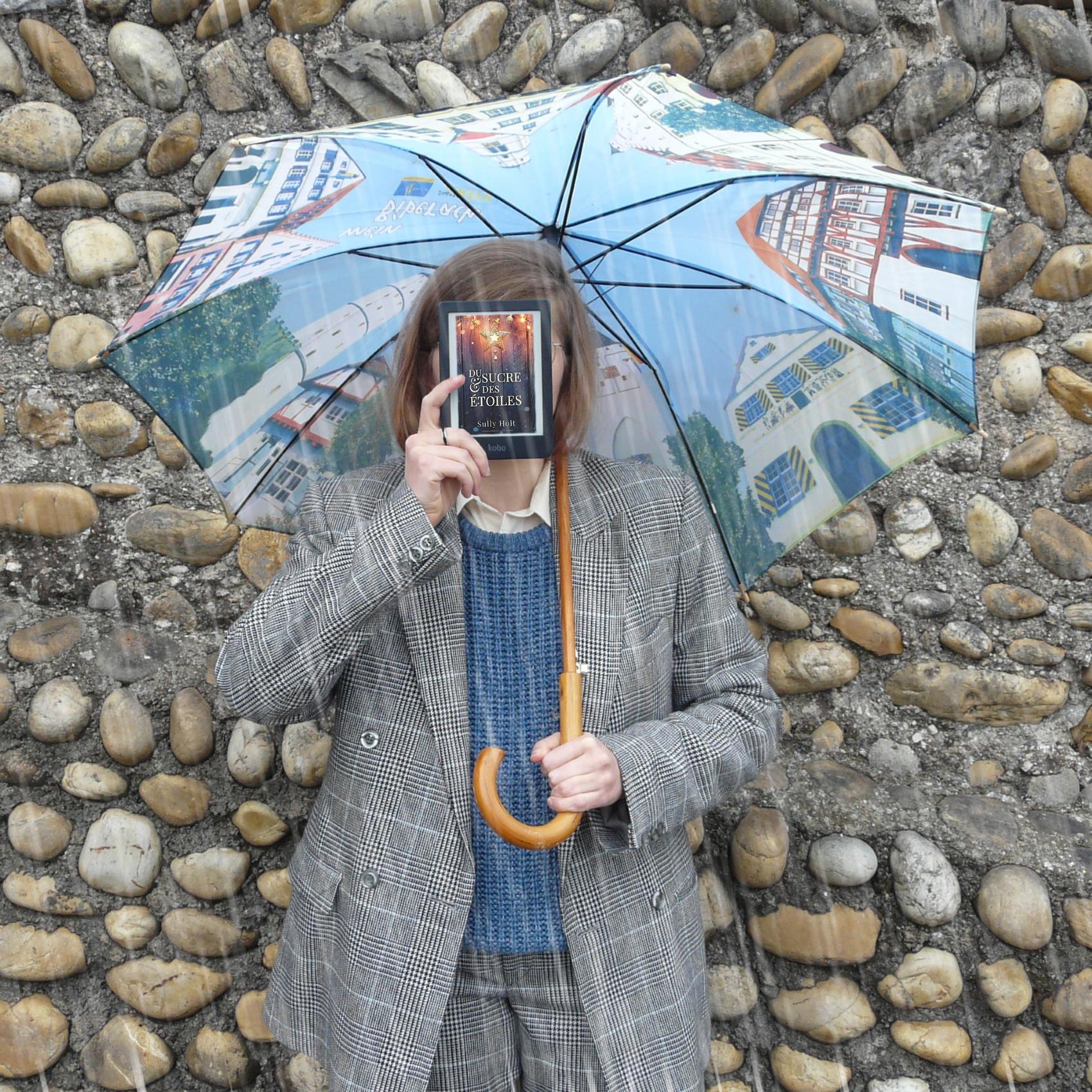 personne en costume gris lisant Du Sucre et des Etoiles sous la pluie, avec un parapluie motif bâtiments