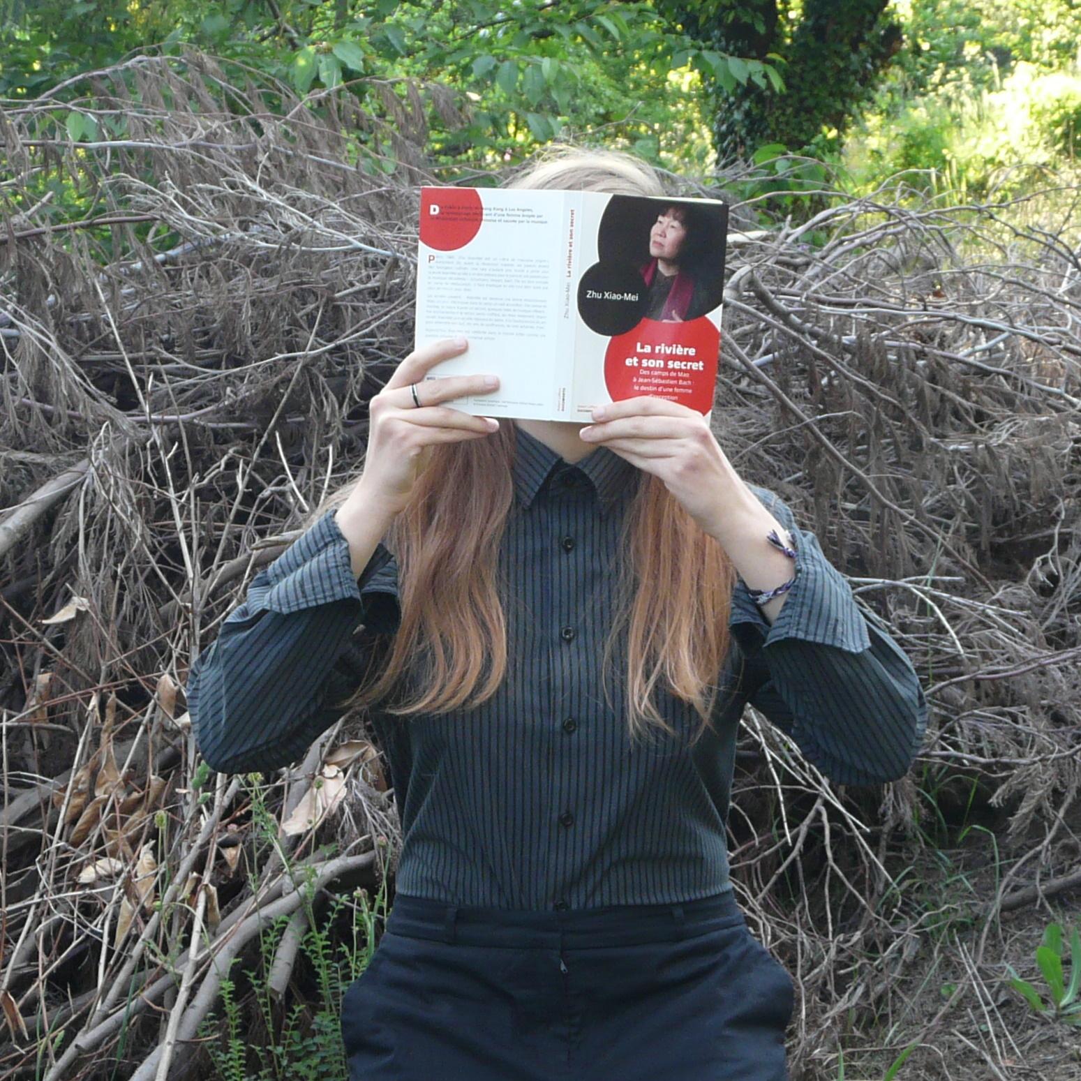 personne en chemise noire lisant La Rivière et son Secret  de Xiao-Mei Zhu devant des fagots