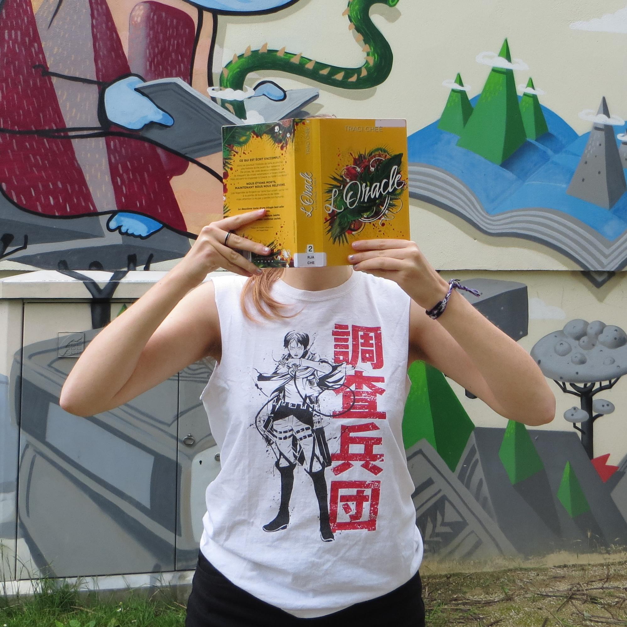 personne en débardeur attack on titan lisant l'oracle de Traci Chee devant une fresque de livres