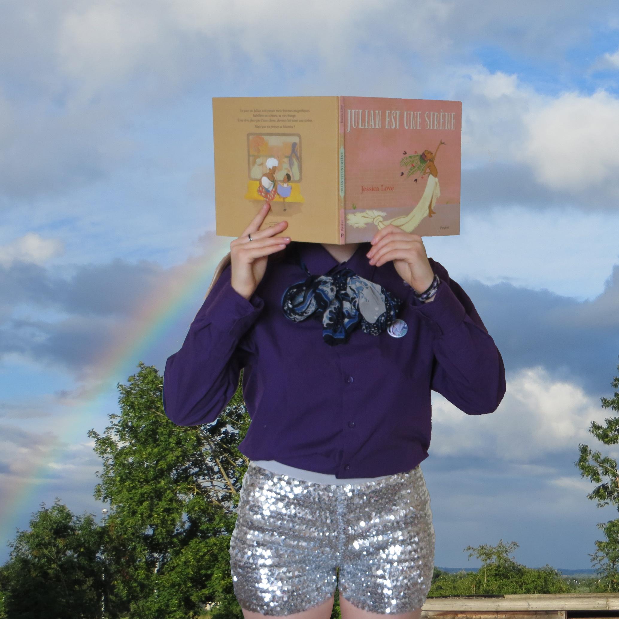 personne en short à paillettes lisant Julian est une Sirène devant un ciel avec un arc-en-ciel