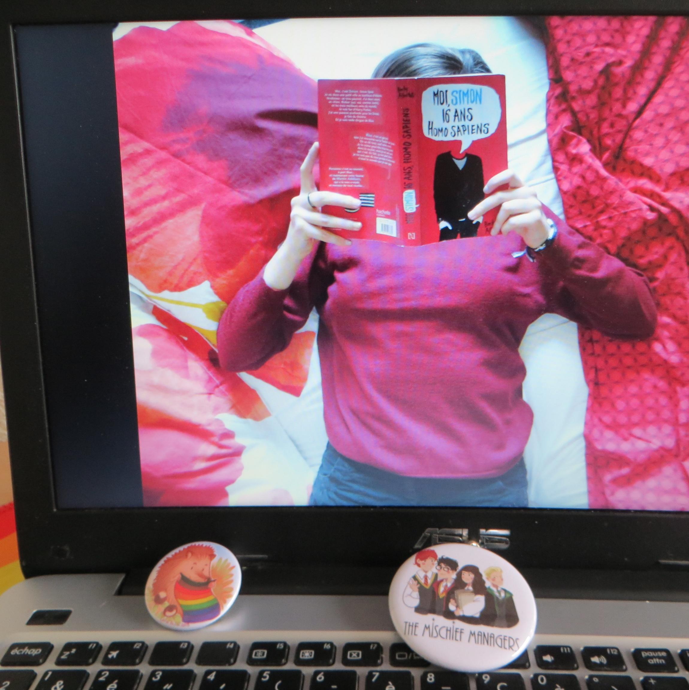 ordinateur affichant une personne en pull lisant Love, Simon   de Becky Albertalli dans un lit