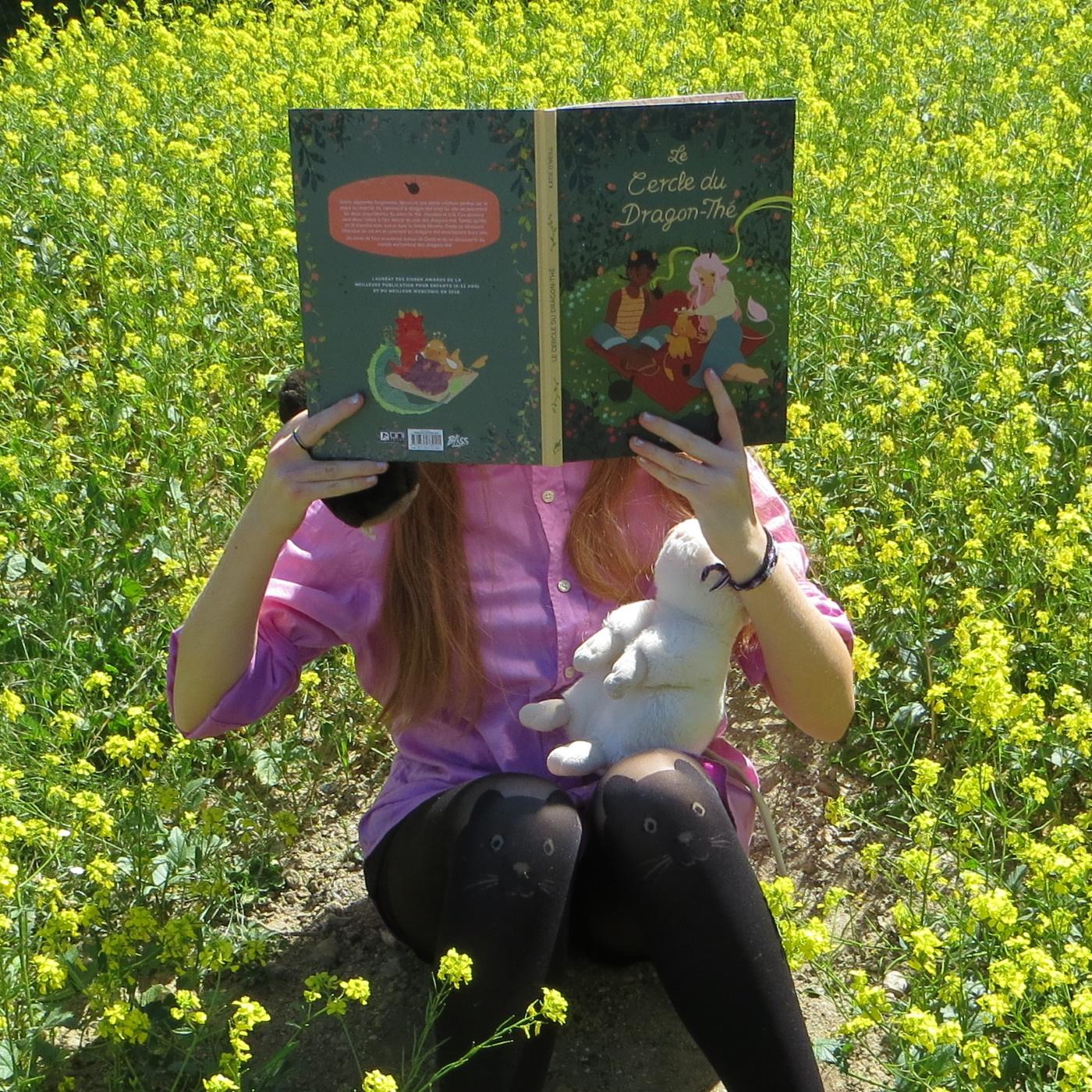personne en chemise rose lisant Le Cercle du dragon-thé de Kay O'Neill avec des peluches dans un champ de fleurs jaunes