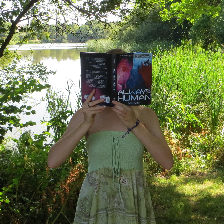 personne en robe verte lisant Always Human devant un lac