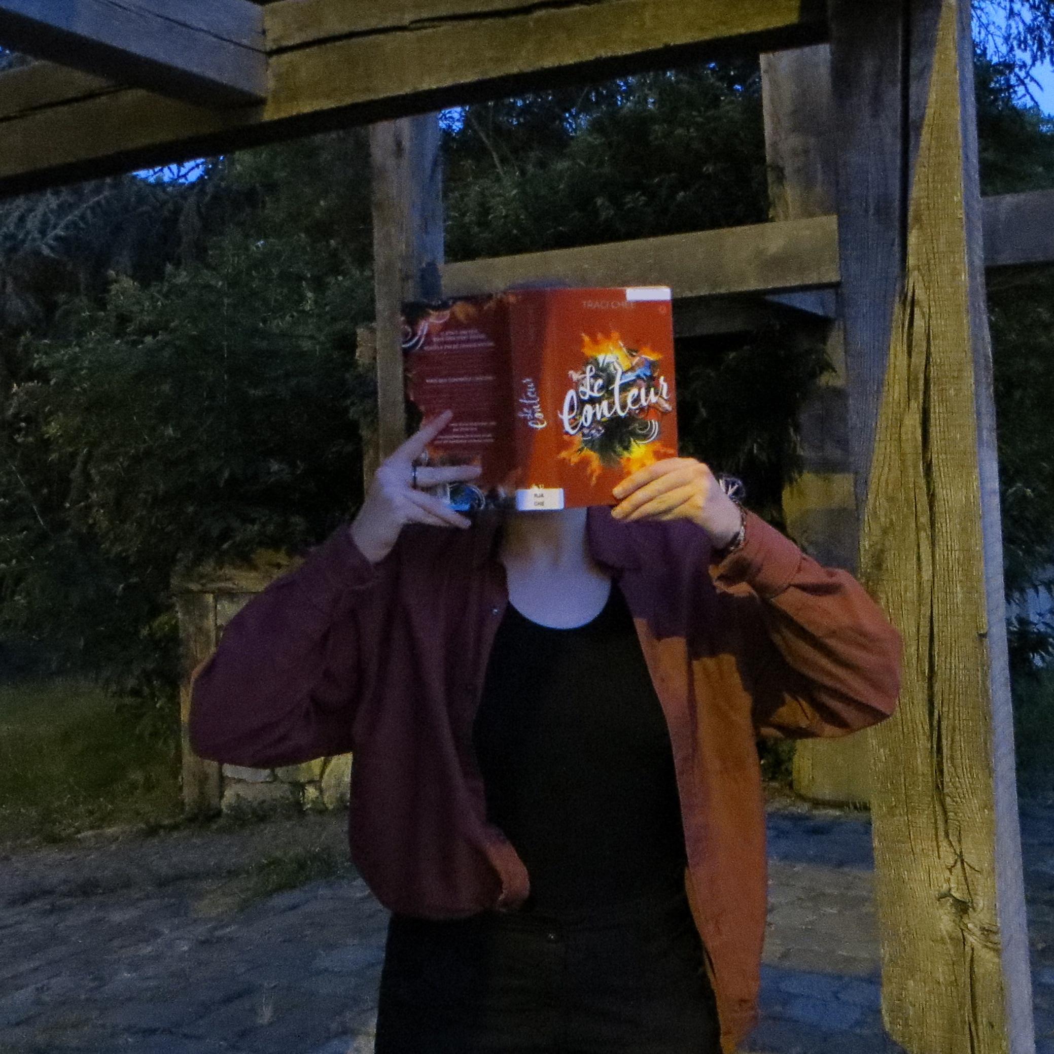 personne en chemise rouge lisant Le conteur de Traci Chee de nuit devant une structure de bois
