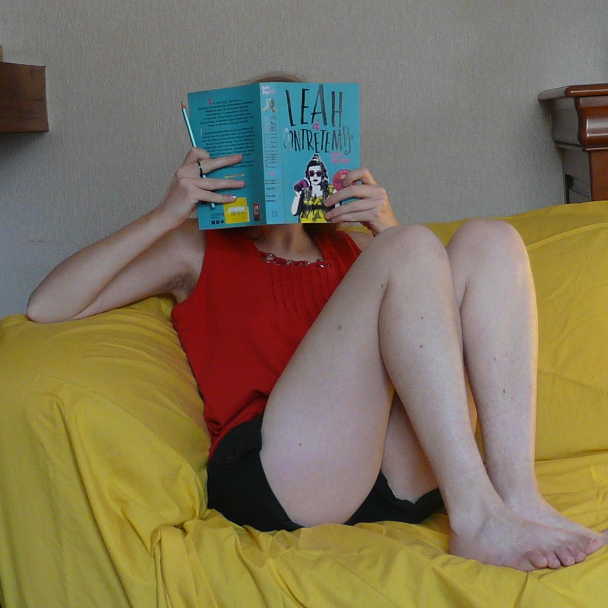 personne lisant Leah à Contretemps de Becky Albertalli dans un canapé