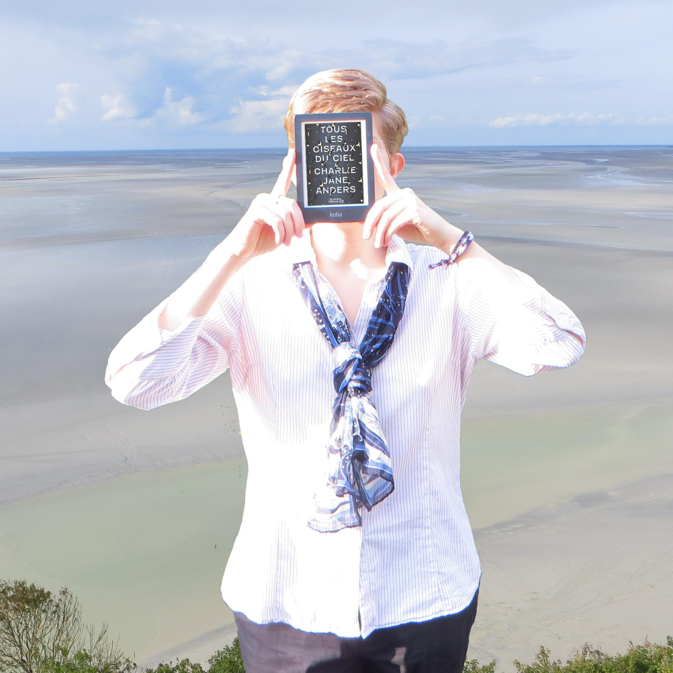 personne en chemise pâle et écharpe La Vague lisant Tous les Oiseaux du Ciel de Charlie Jane Anders devant la plage