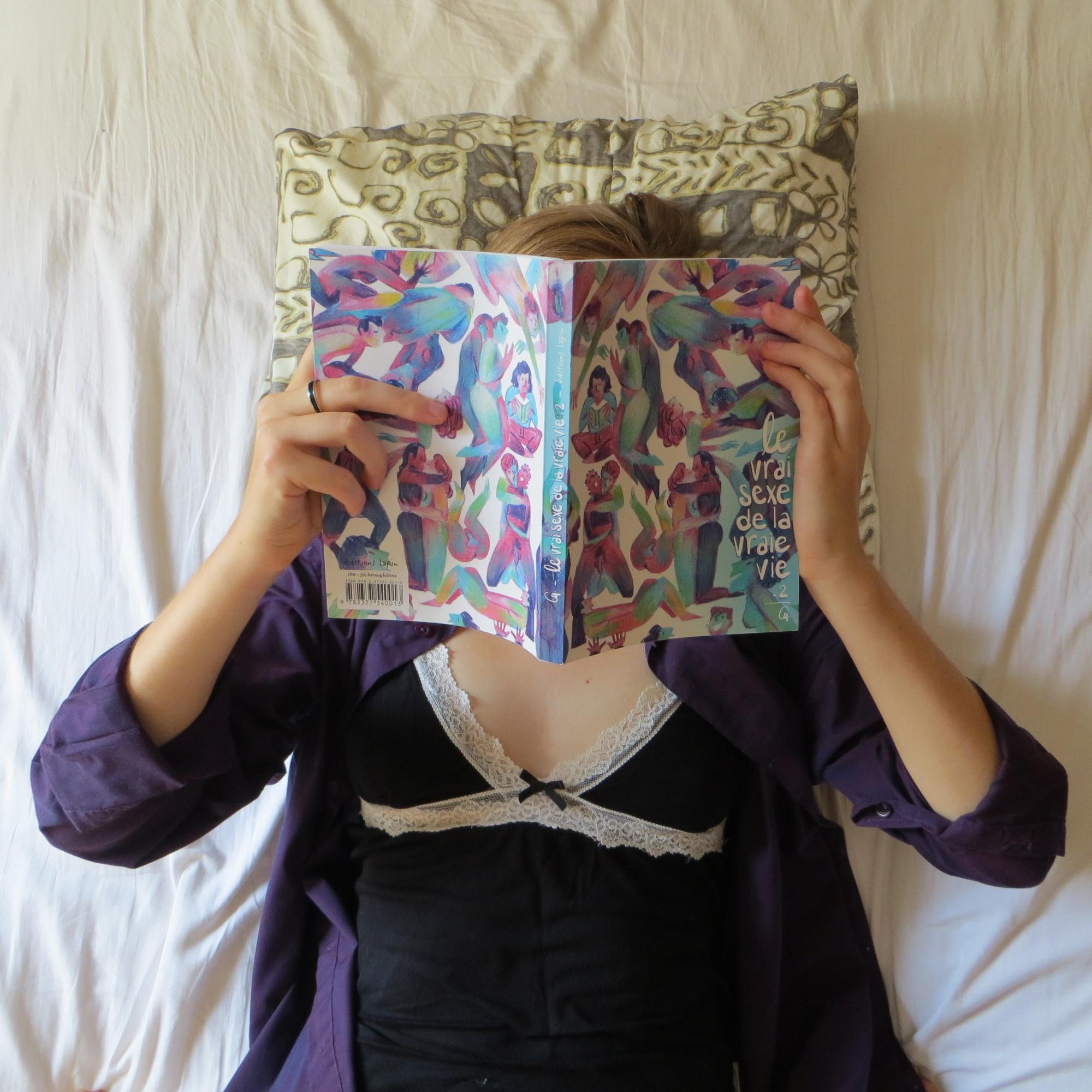 personne en nuisette et chemise lisant Le vrai sexe de la vraie vie tome 2 de Cy dans son lit