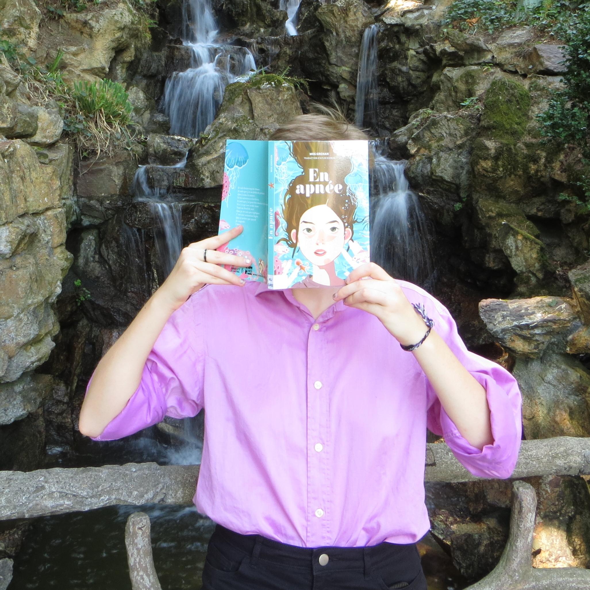personne en chemise rose lisant En Apnée de Meg Grehan devant une cascade