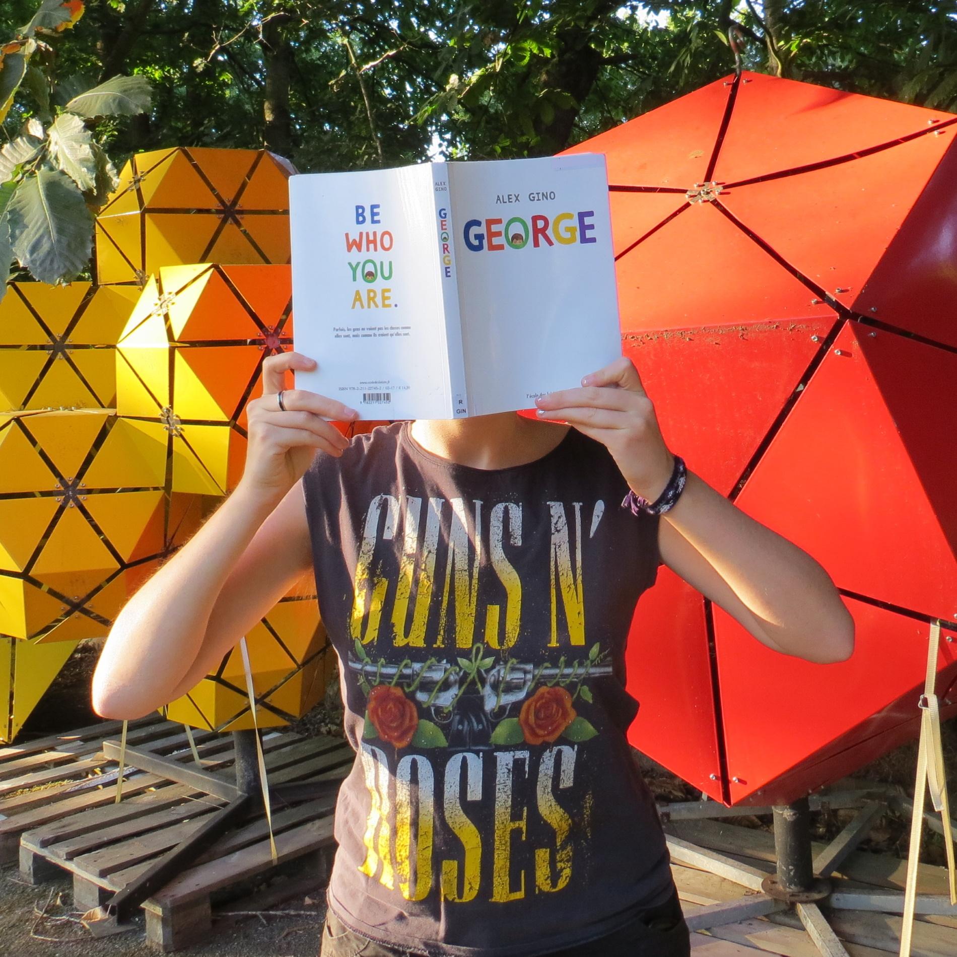 personne lisant George d'Alex Gino devant des structures multicolores