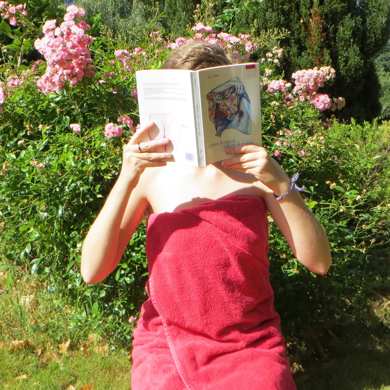 personne enroulée dans une serviette rouge lisant Corps à Cœur Cœur à Corps de Léa Castor devant des roses