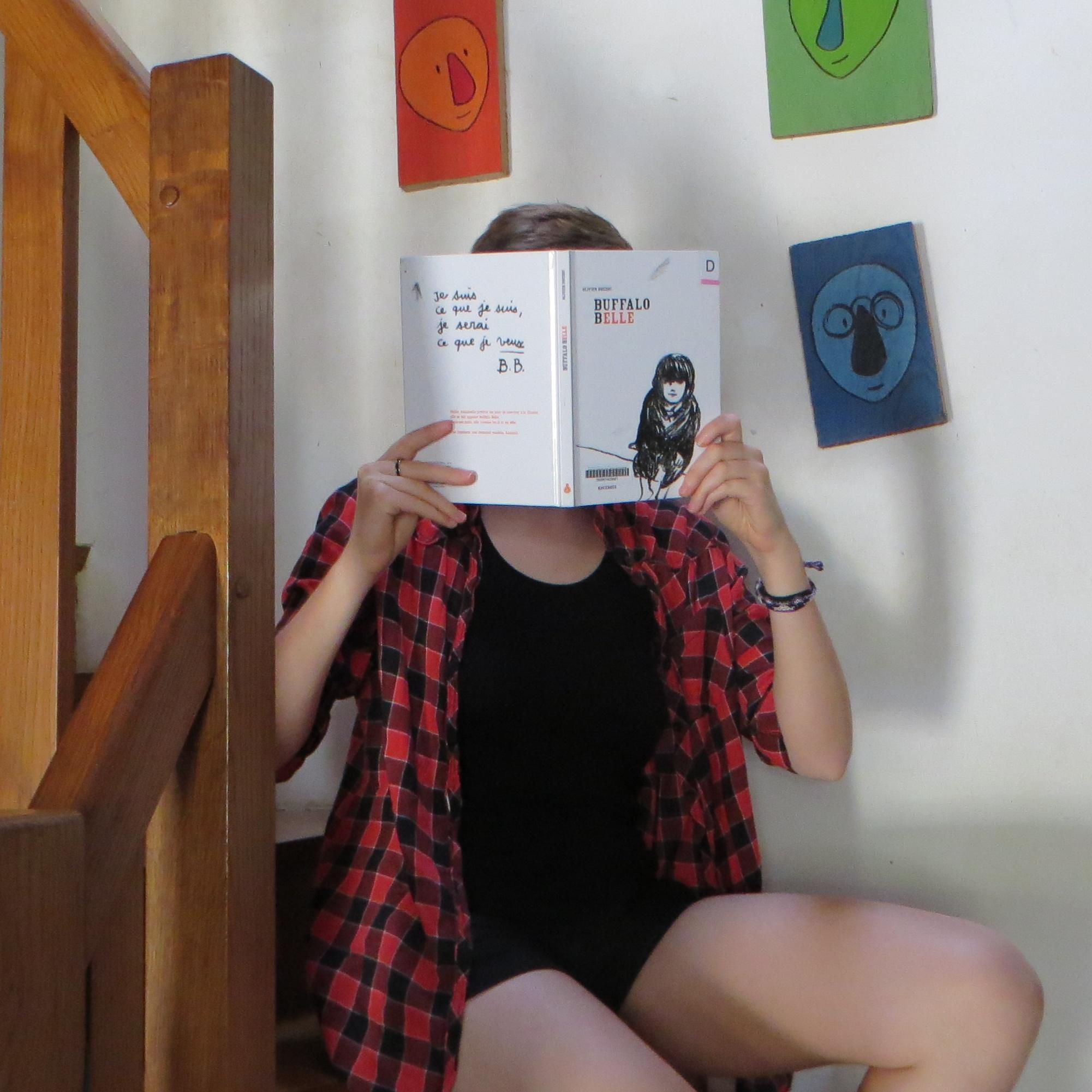 personne lisant Buffalo Belle d'Olivier Douzou dans des escaliers en bois