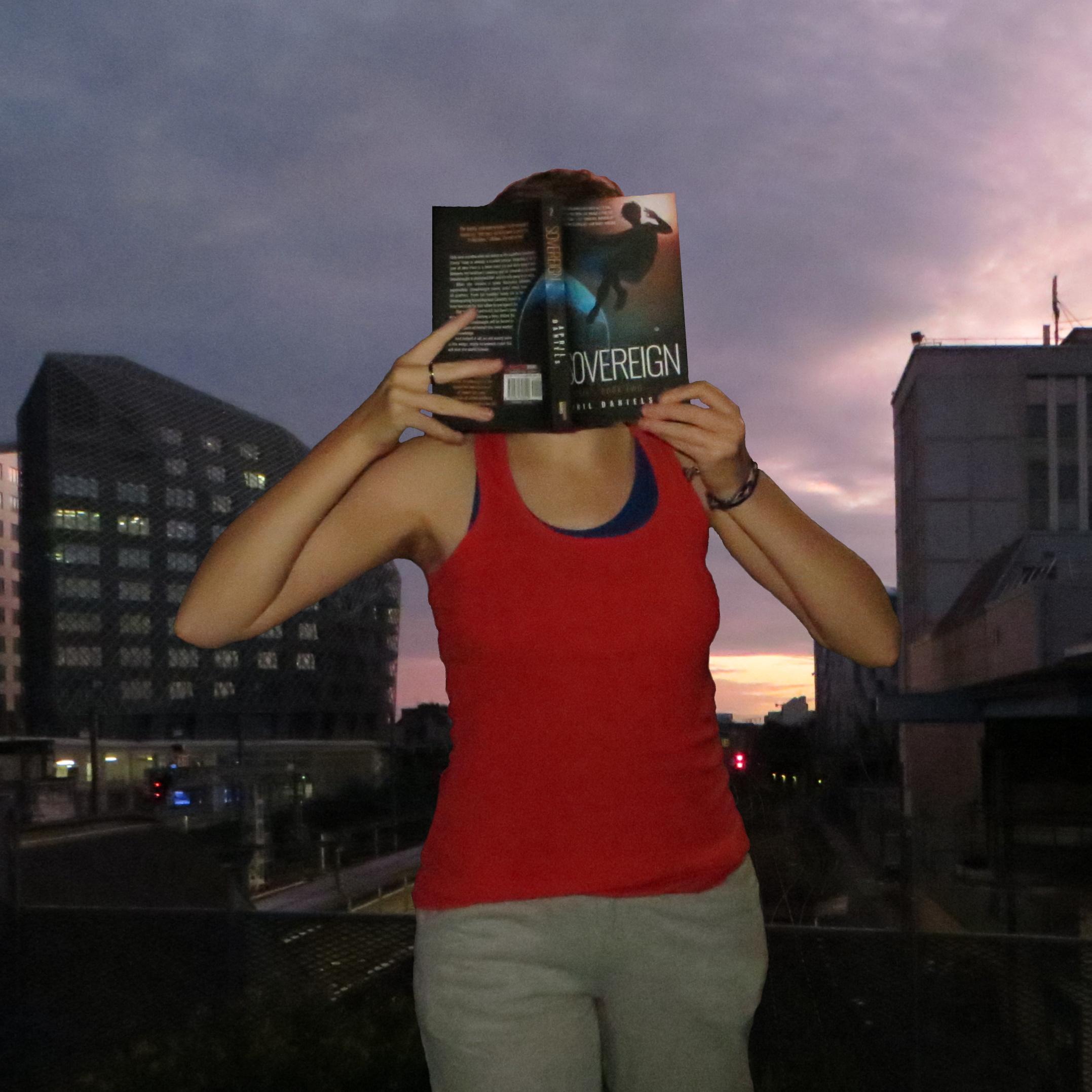 personne en débardeur rouge lisant Sovereign d'April Daniels devant des rails, le soleil se couche