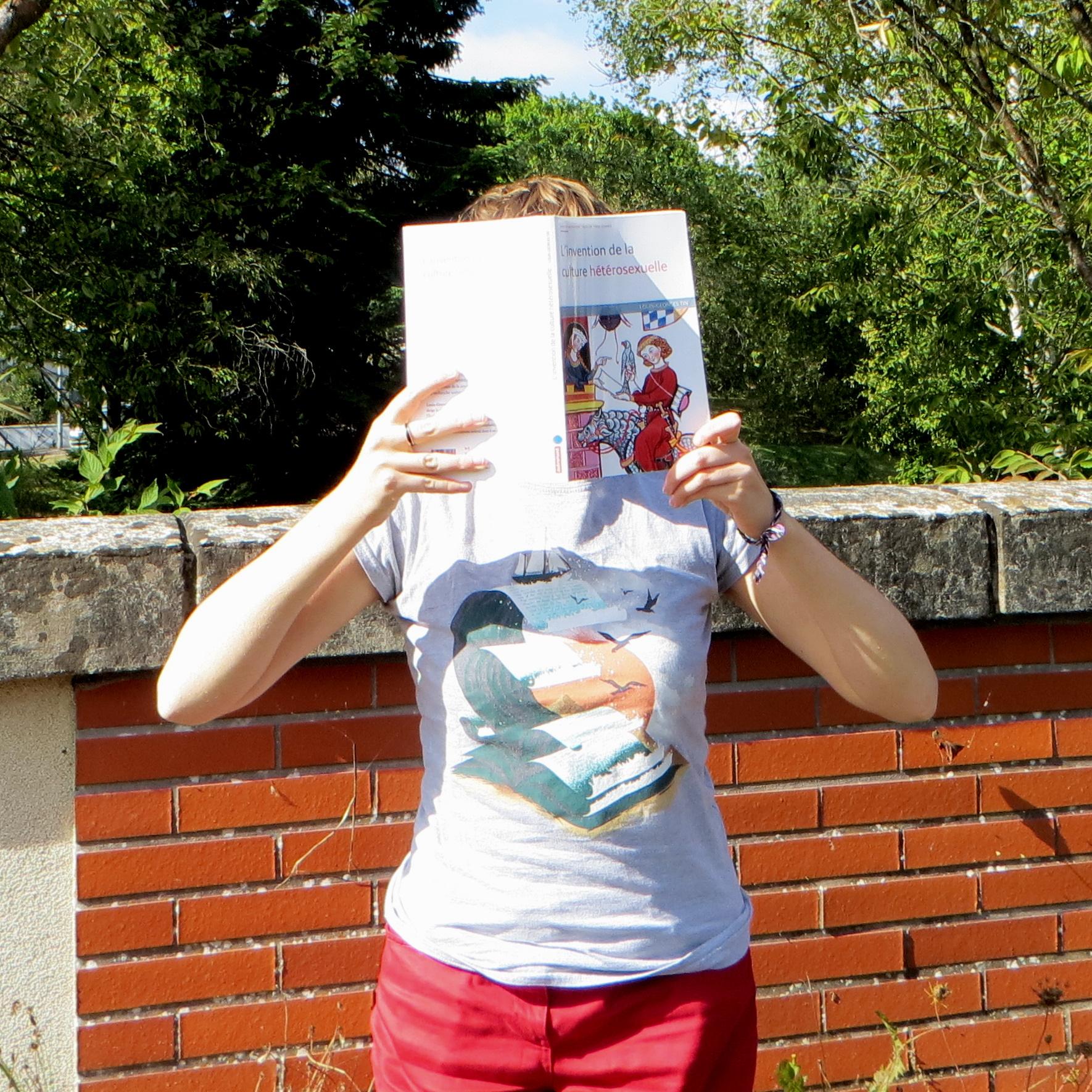 personne en t-shirt littéraire lisant L'invention de la Culture Hétérosexuelle de Louis-Georges Tin devant un pont de briques