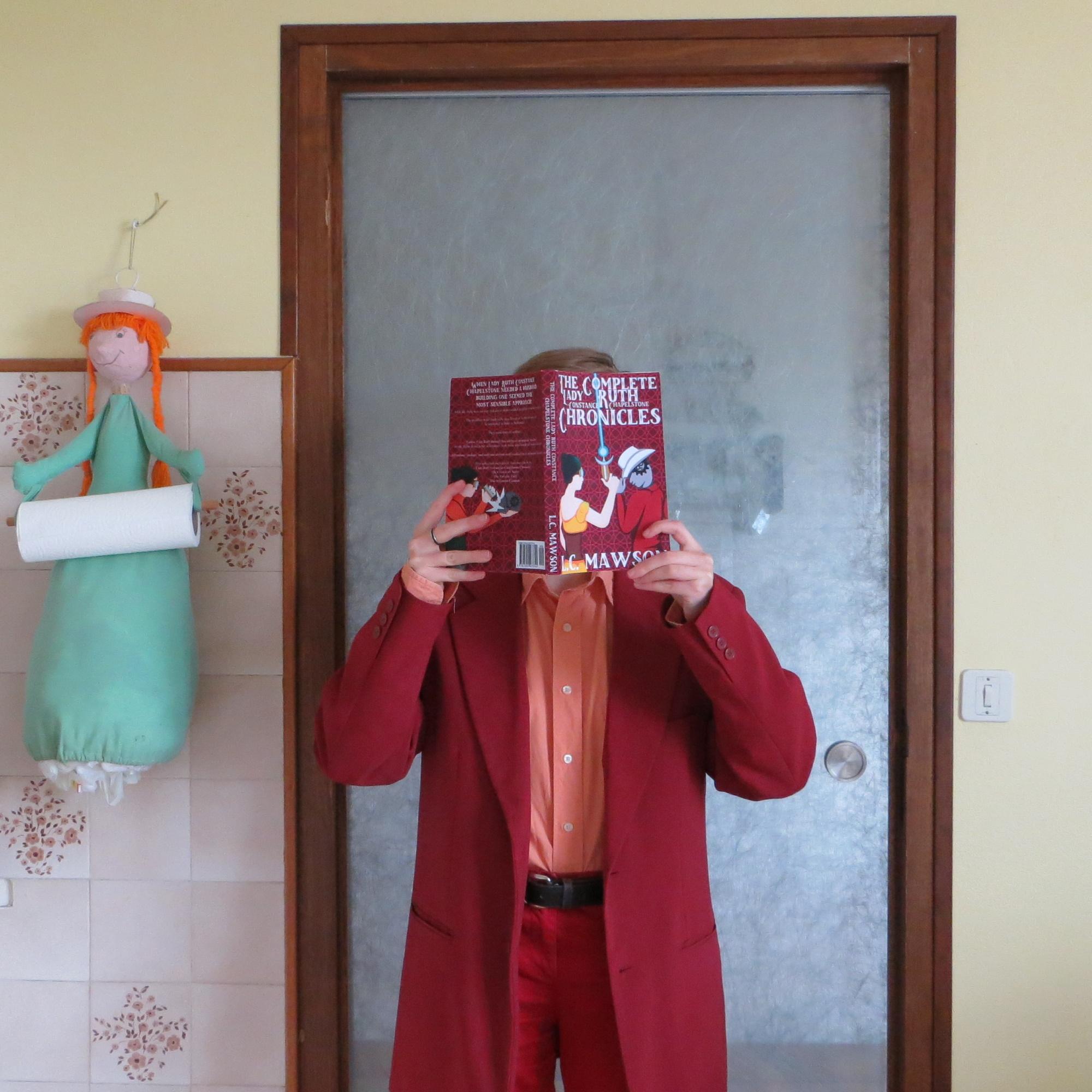 personne en rouge lisant Lady Ruth Constance Chapelstone Chronicles de L.C. Mawson devant un mur jaune vif