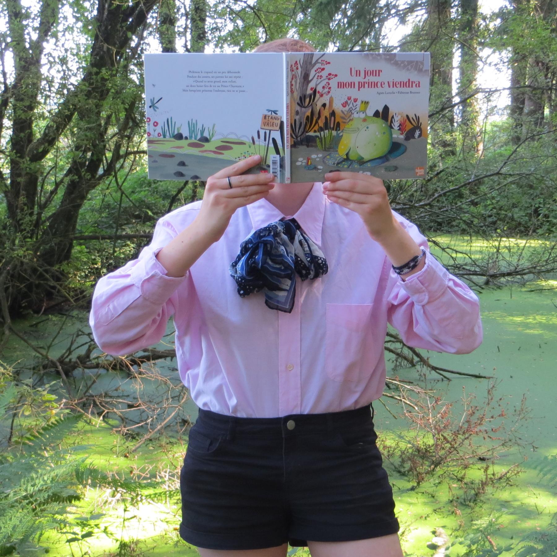 Personne en short et en chemise rose à jabot lisant Un Jour mon Prince viendra d'Agnès Laroche devant un étang