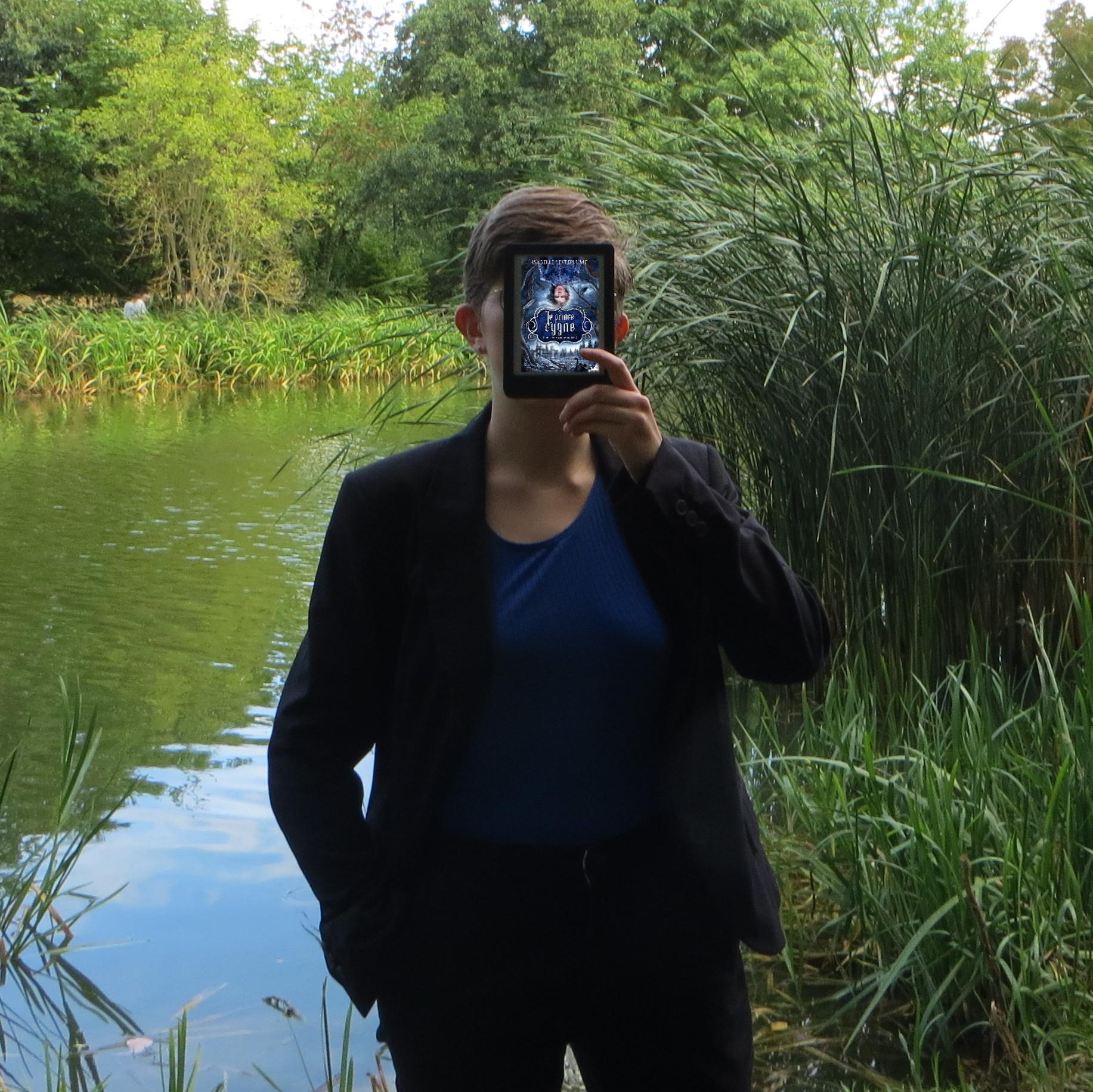 personne en débardeur bleu et veste noire lisant Le prince cygne d'Isabelle Lesteplume devant un lac