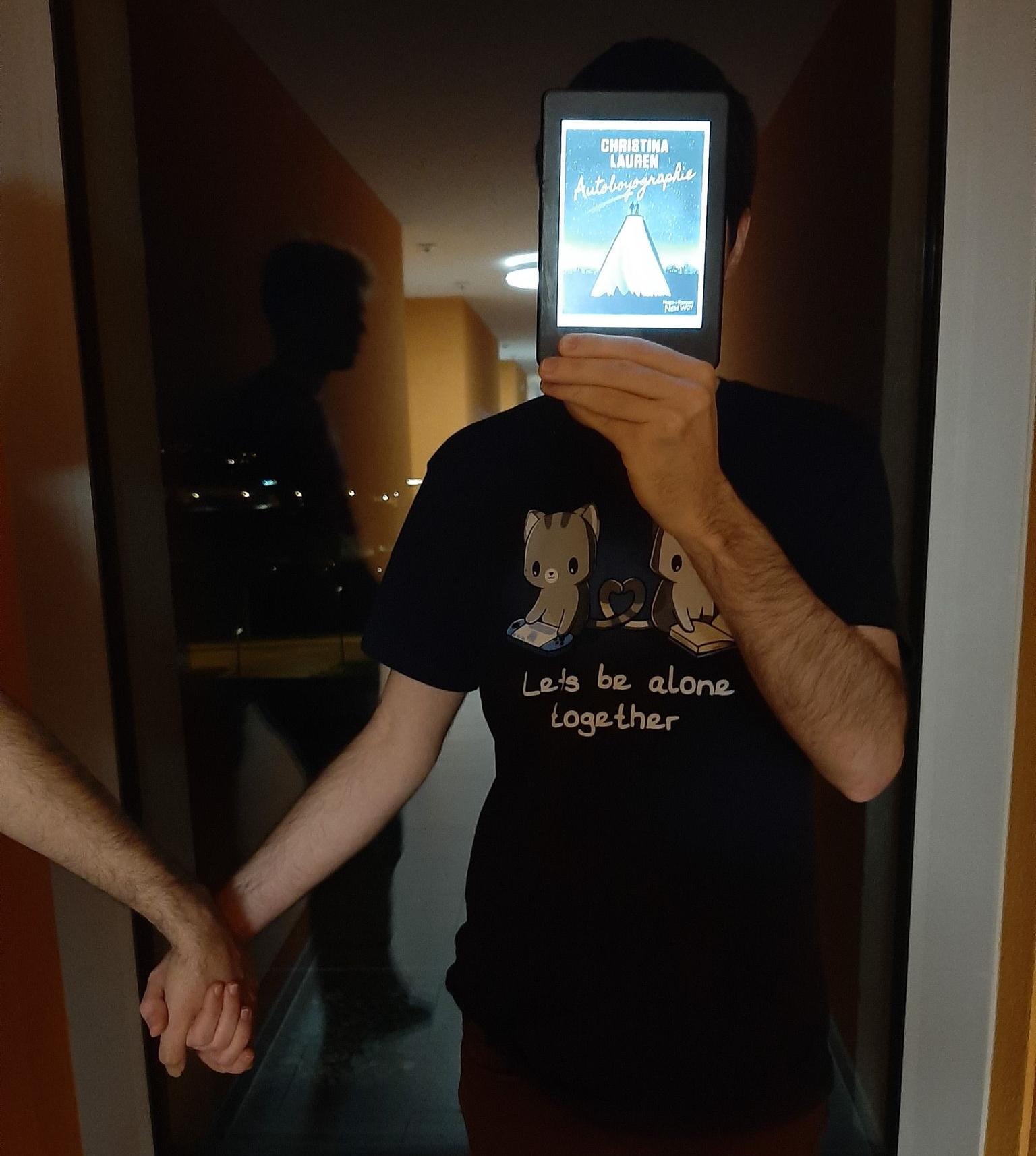 homme tenant une liseuse avec la couverture d'autoboyographie de Christina Lauren devant son visage dans une pièce sombre, tenant la main d'une autre personne. La vitre derrière montre le reflet d'une silhouette masculine