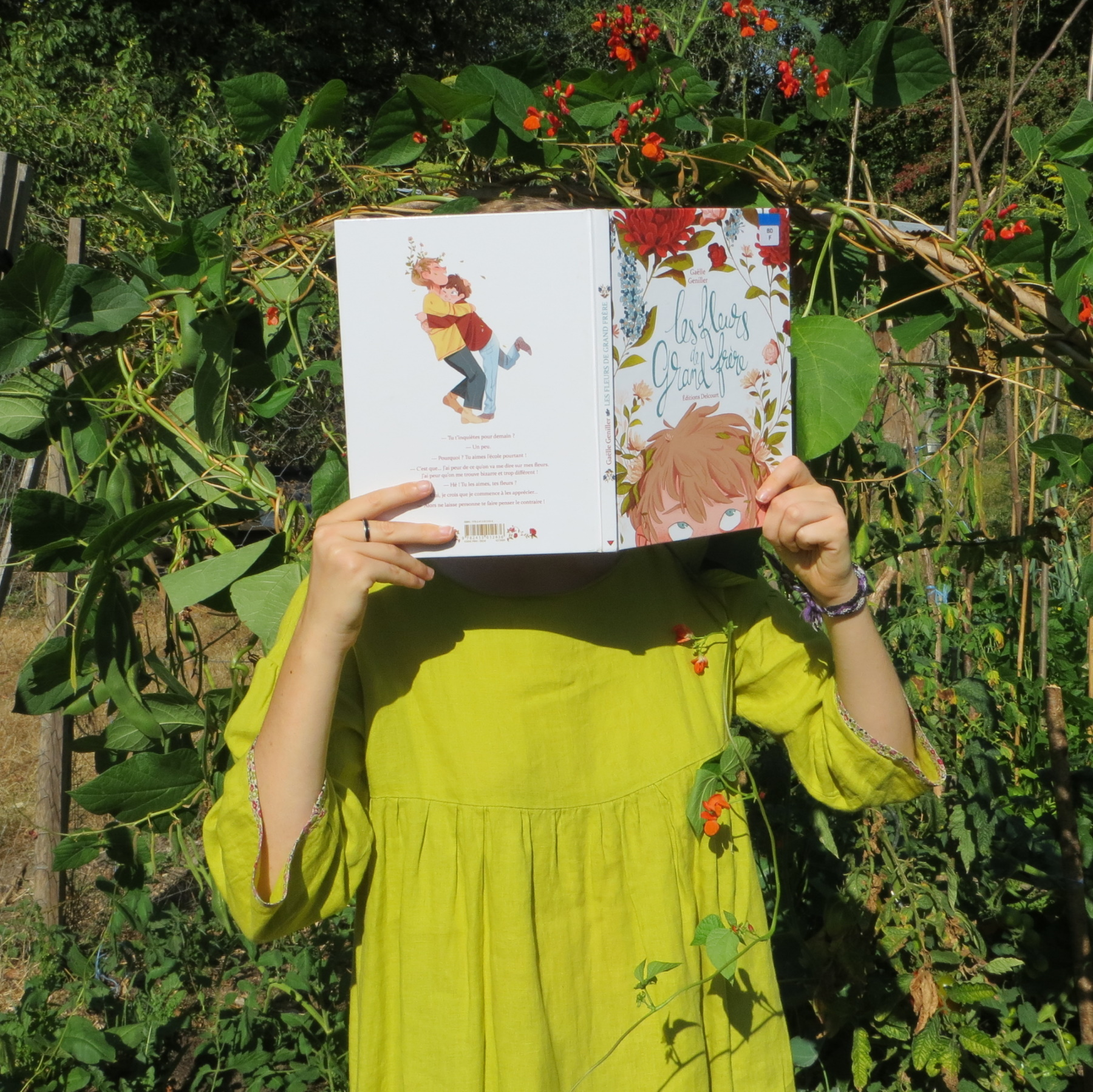 personne en tunique verte lisant Les fleurs de grand-frère de Gaëlle Geniller entourée de plantes grimpantes