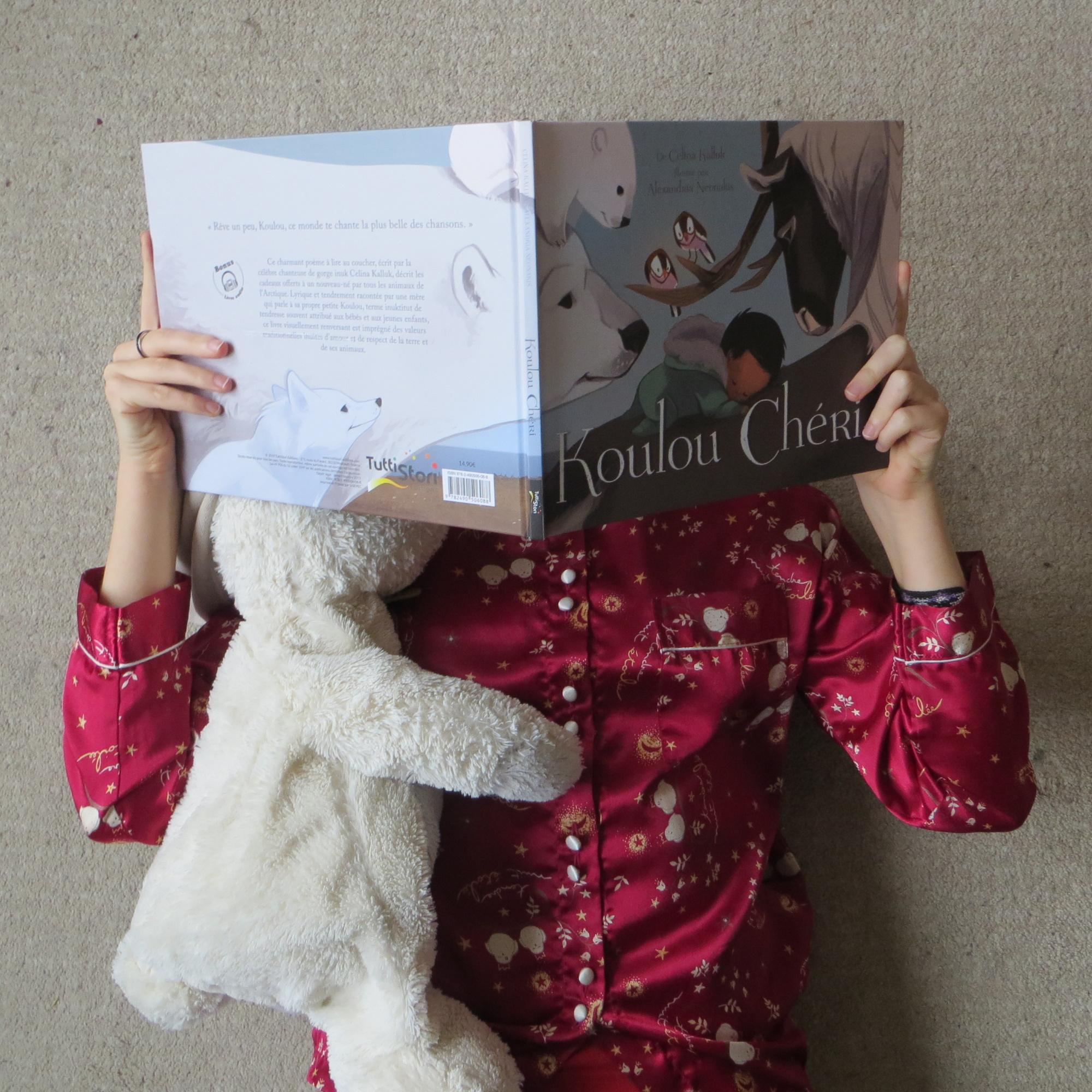 personne en pyjama lisant Koulou chéri de Celina Kalluk & Alexandria Neonakis sur un tapis blanc avec une peluche de lapin