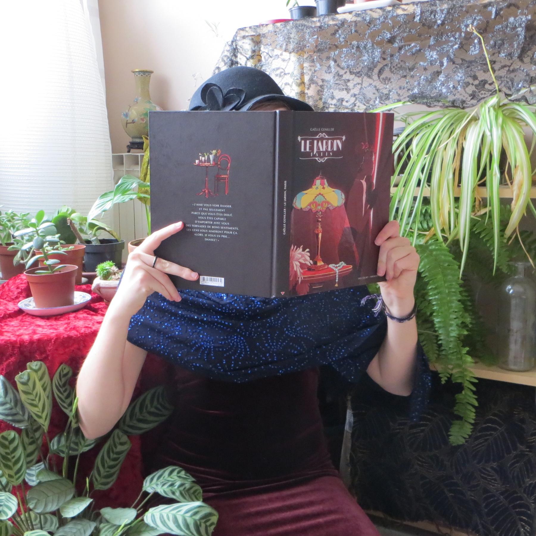 personne en robe à paillettes vintage lisant Le jardin Paris de Gaëlle Geniller devant une table couverte de plantes