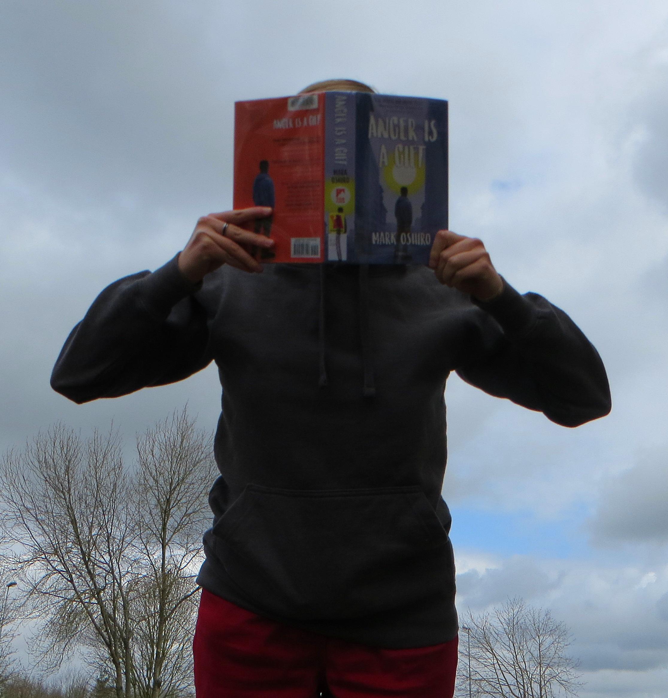 personne en pull gris lisant Anger is a Gift de Mark Oshiro devant un ciel gris, la photo est prise en contreplongée et la personne a l'air menaçante