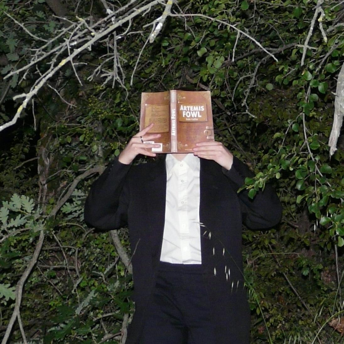 personne en costume noir et blanc lisant Artémis Fowl d'Eoin Colfer de nuit, devant des arbres