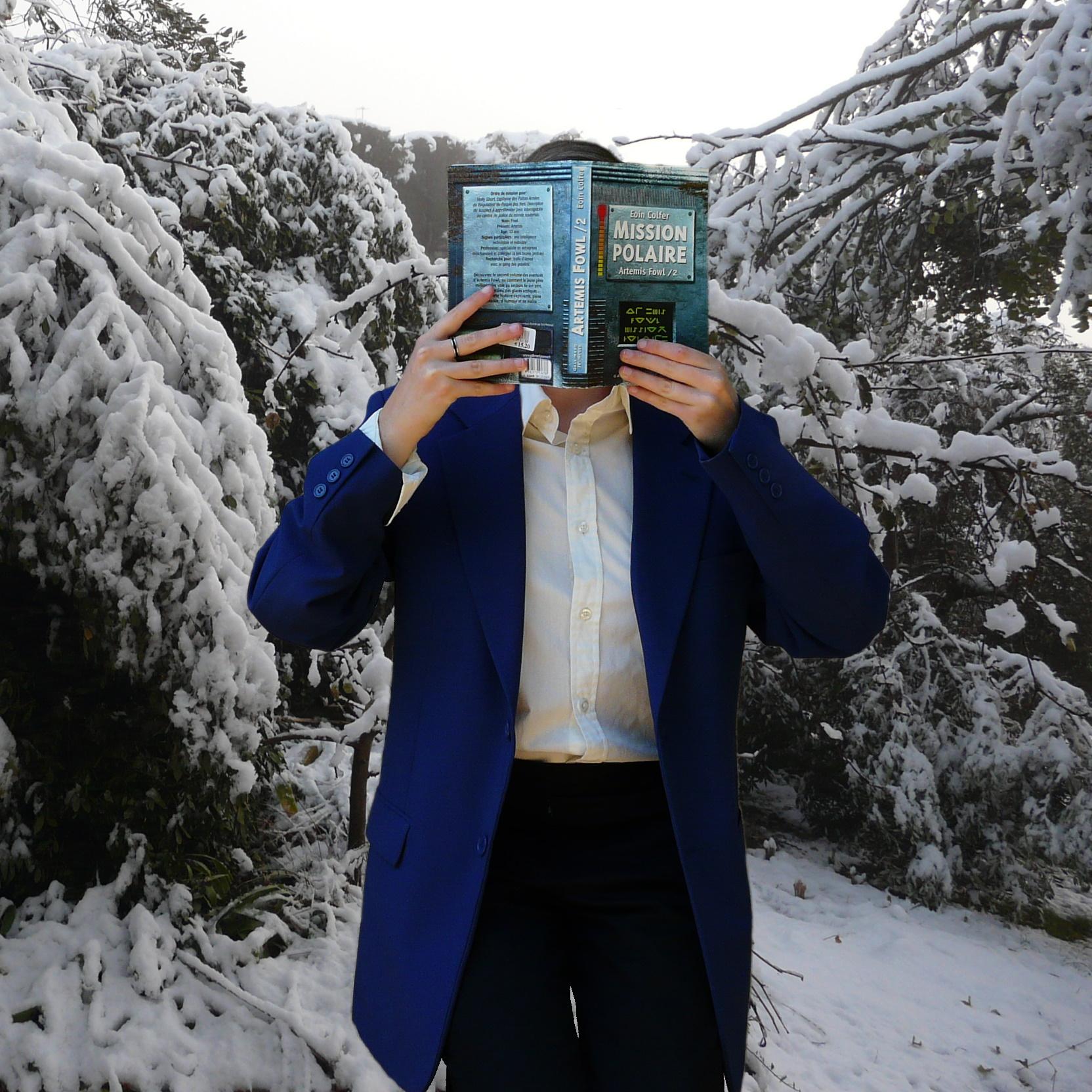 personne en costume bleu lisant Artémis Fowl : Mission Polaire d'Eoin Colfer dans la neige