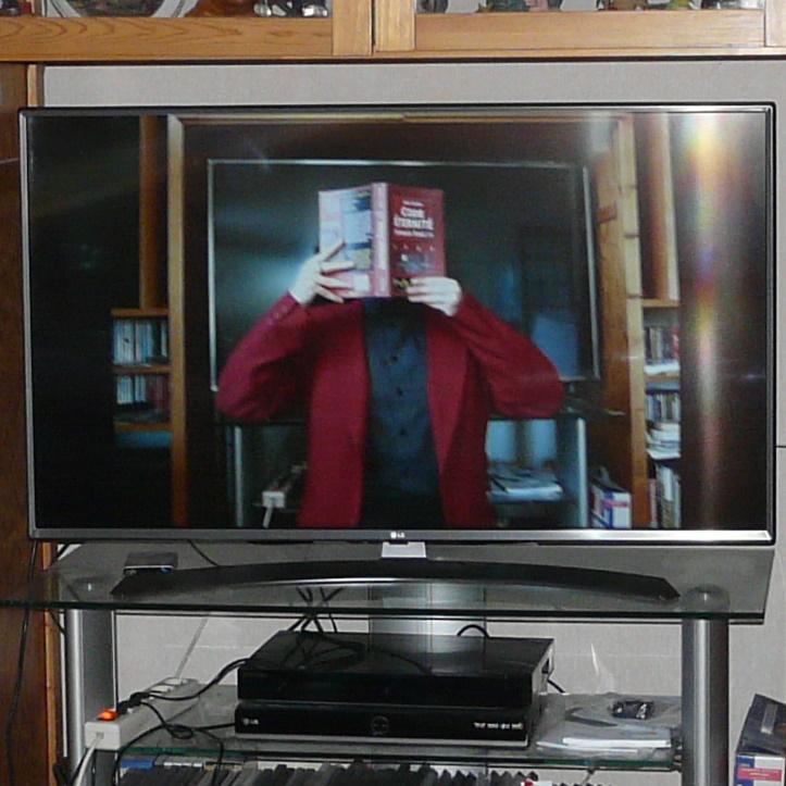 télévision affichant une personne en costume rouge lisant Code Eternité d'Eoin Colfer