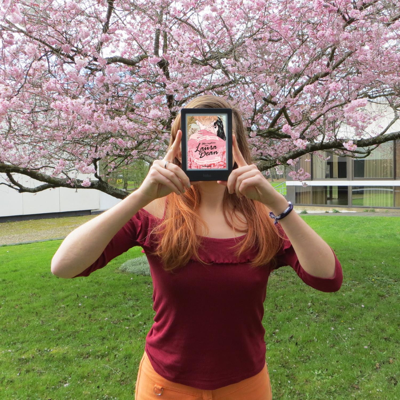 personne en tenue rouge et orange lisant Mes ruptures avec Laura Dean de Mariko Tamaki devant un arbre en fleurs roses