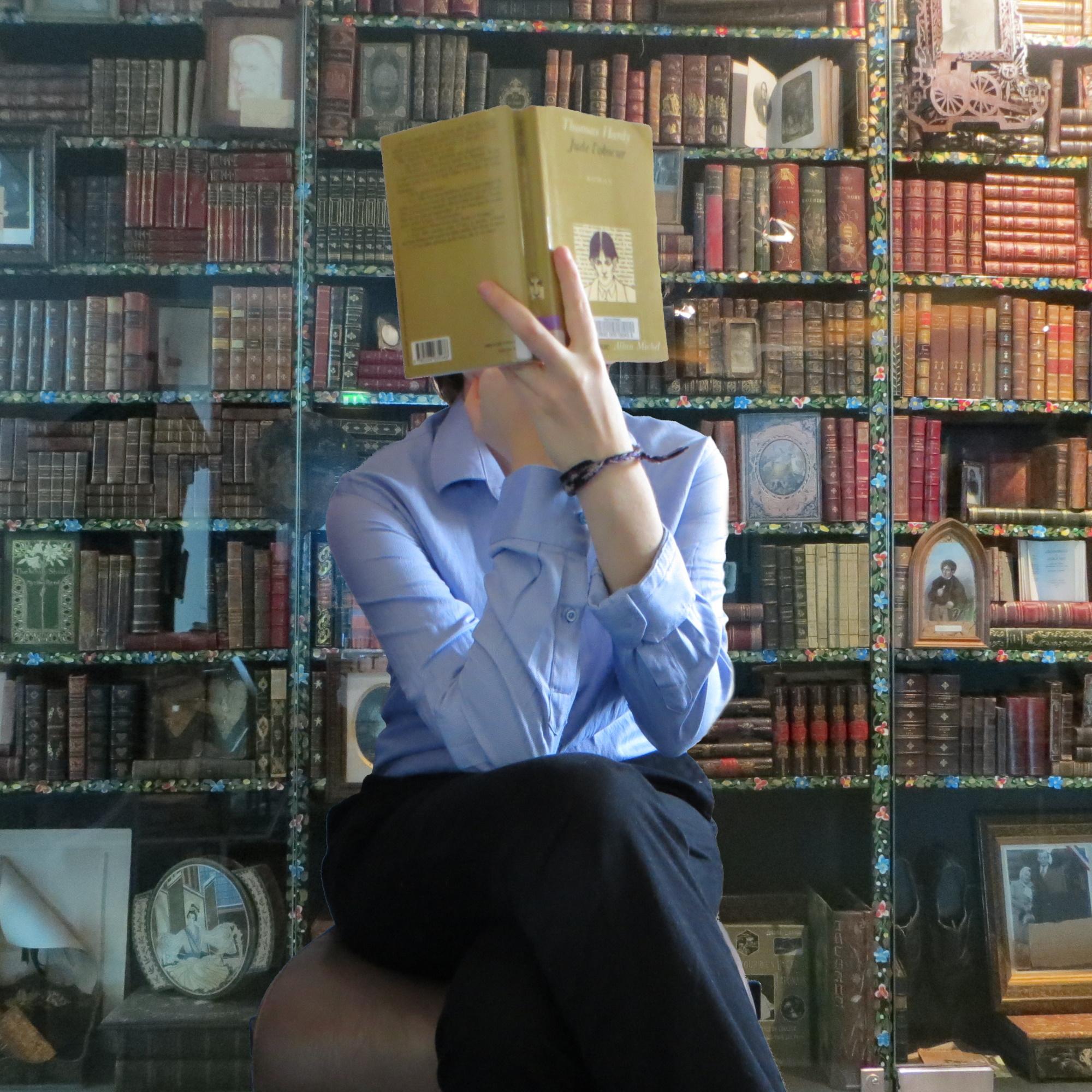 personne en chemise lisant Jude l'Obscur de Thomas Hardy devant une vieille bibliothèque pleine de grimoires