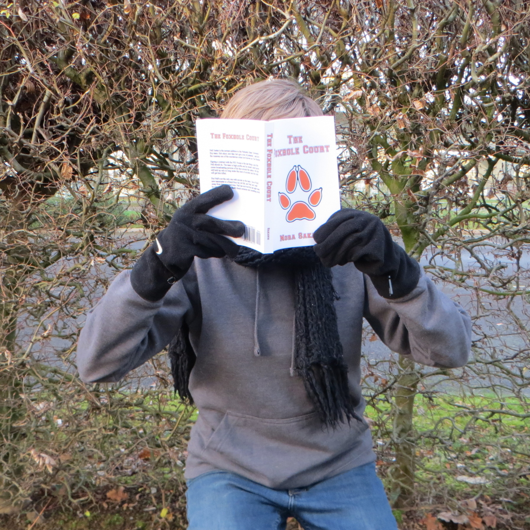 personne en pull et écharpe lisant All for the Game tome 1 : The Foxhole Court de Nora Sakavic devant une haie effeuillée