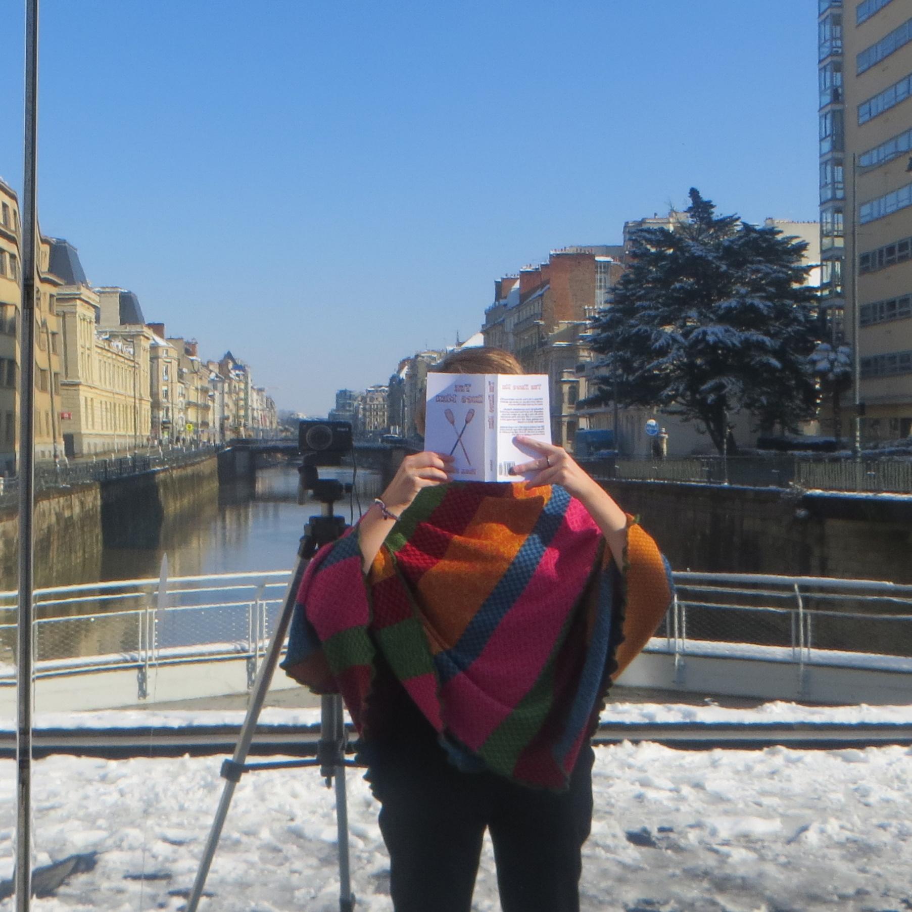 photo prise dans un miroir d'une personne en poncho multicolore lisant All For The Game 3 : The King's Men de Nora Sakavic devant un fleuve aux berges enneigées