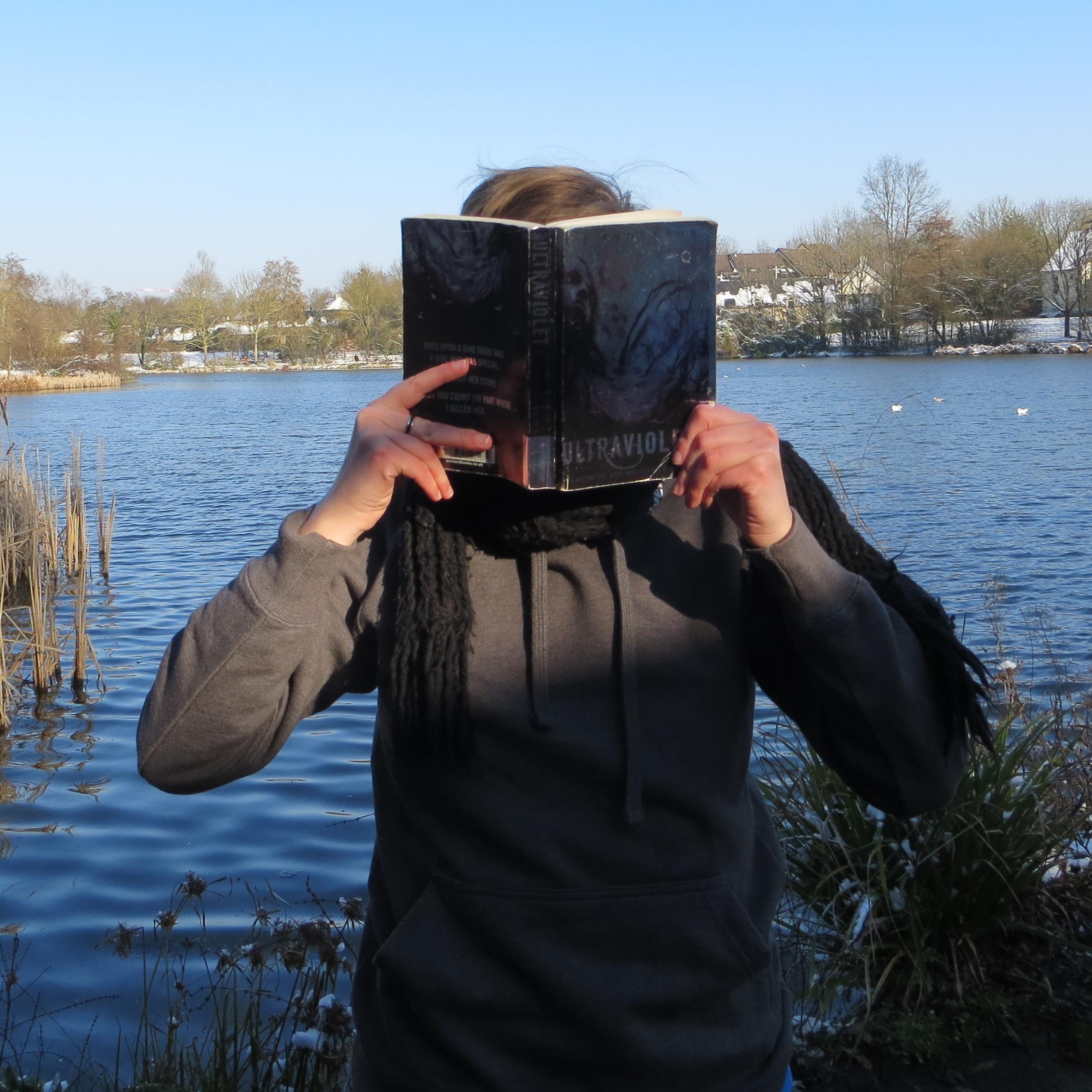 personne en pull gris lisant Ultraviolet de R.J. Anderson devant un lac aux berges enneigées