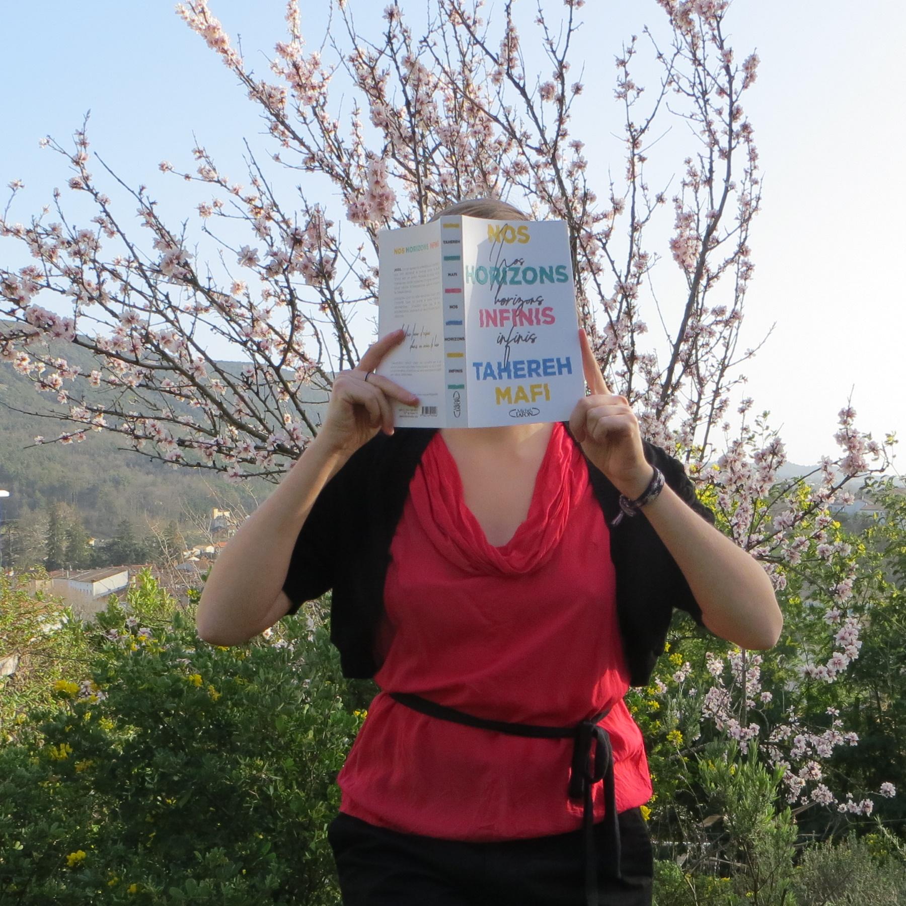 personne en débardeur rouge lisant Nos Horizons Infinis de Tahereh Mafi devant un amandier en fleurs